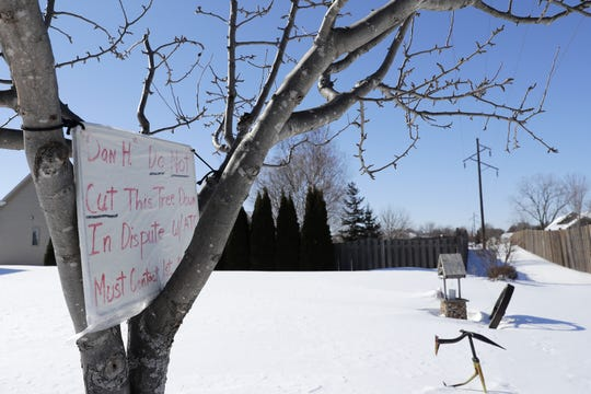 Homeowners Donna and Larry Chaudoir have displayed a sign in the dwarf pear tree they are seeking to save from being removed from their backyard due to planned power line work by American Transmission Co. in the McAuliffe Park neighborhood on Green Bay's east side.