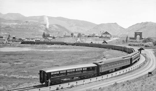 A special train carrying military veterans stands at the Northern Pacific's terminal at the northern gateway to Yellowstone National Park. The nearly circular track makes it possible to turn the whole train. The railroad area in the photo is now the Gardiner High School football field and running track.