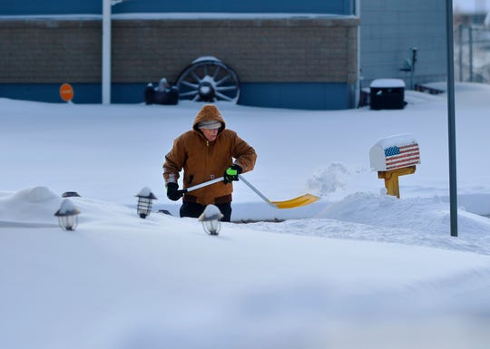 Les Taylor of Great Falls clears snow from the sidewalks around his house in February, which was the city's third snowiest on record and the second coldest.