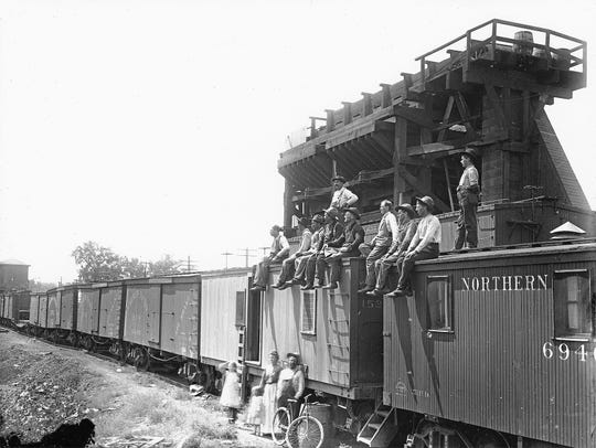 "Folks pose with Northern Pacific boxcars converted to living quarters, perhaps in or near Miles City.""Extra gangs"" worked on track projects that were too large for regular section crews."