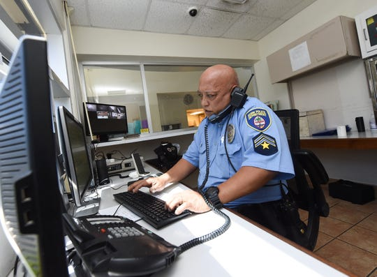 Guam Police Department officer M.C. Terlaje, a desk watch officer at his department's Tumon-Tamuning Precinct, takes a call during his shift on Friday. The administration's transition team report recommends supplementing the police department with volunteers.