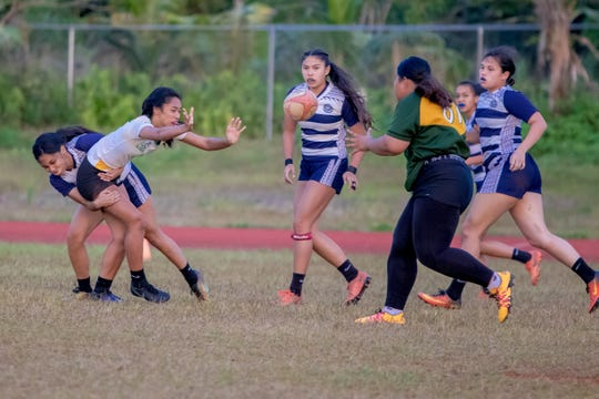 A John F. Kennedy High School player passes the ball to teammate a she gets tackled down during the girls rugby game held at Okkodo High School on Feb. 14.
