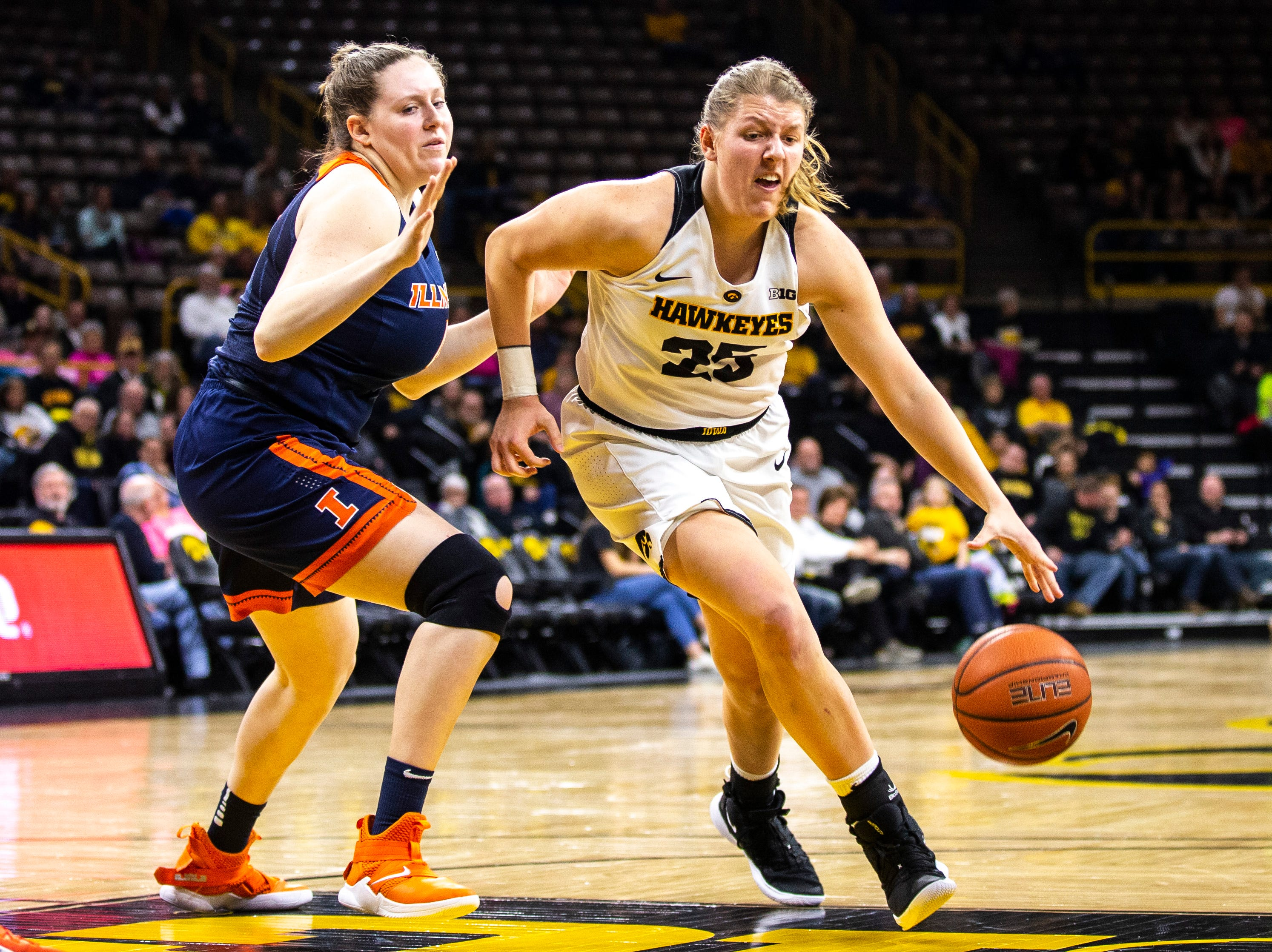 Iowa's Monika Czinano (25) drives to the basket while Illinois forward Alex Wittinger, left, defends during a NCAA Big Ten Conference women's basketball game on Thursday, Feb. 14, 2019 at Carver-Hawkeye Arena in Iowa City, Iowa.