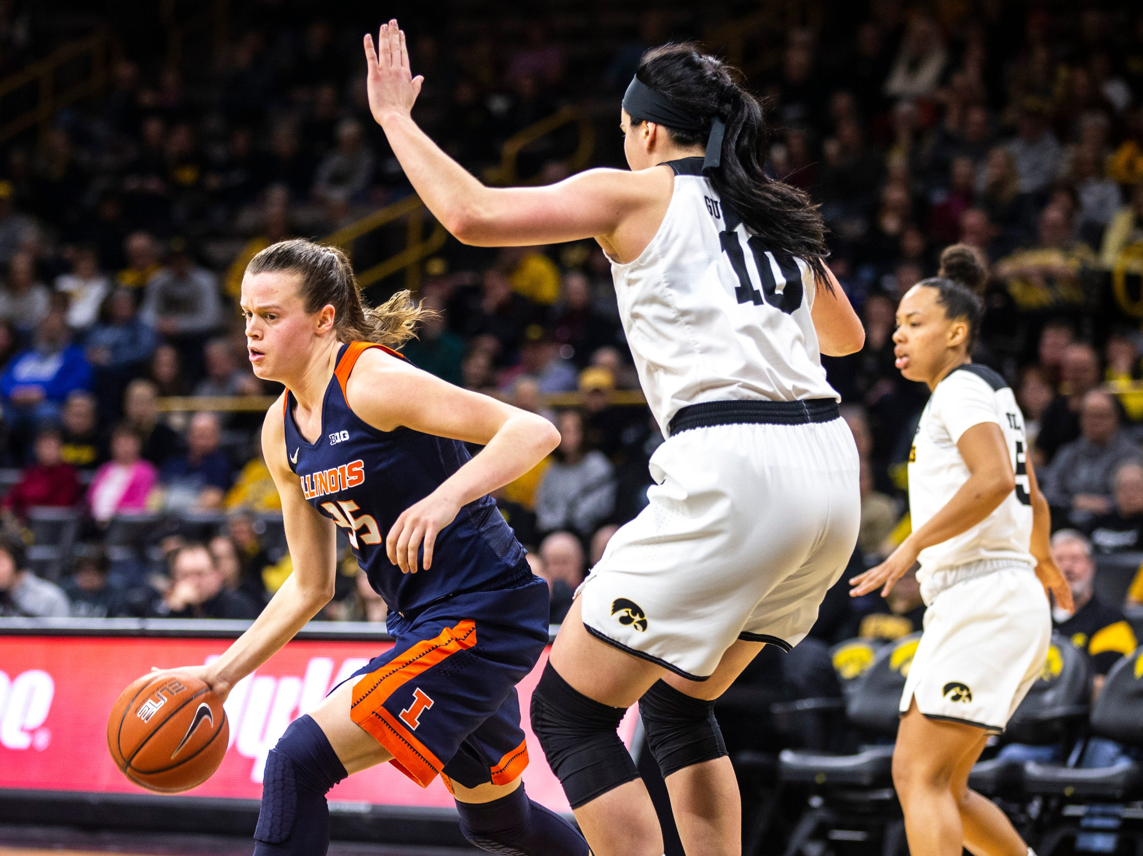 Illinois forward Alex Wittinger (35) takes the ball up court while Iowa center Megan Gustafson (10) defends during a NCAA Big Ten Conference women's basketball game on Thursday, Feb. 14, 2019 at Carver-Hawkeye Arena in Iowa City, Iowa.