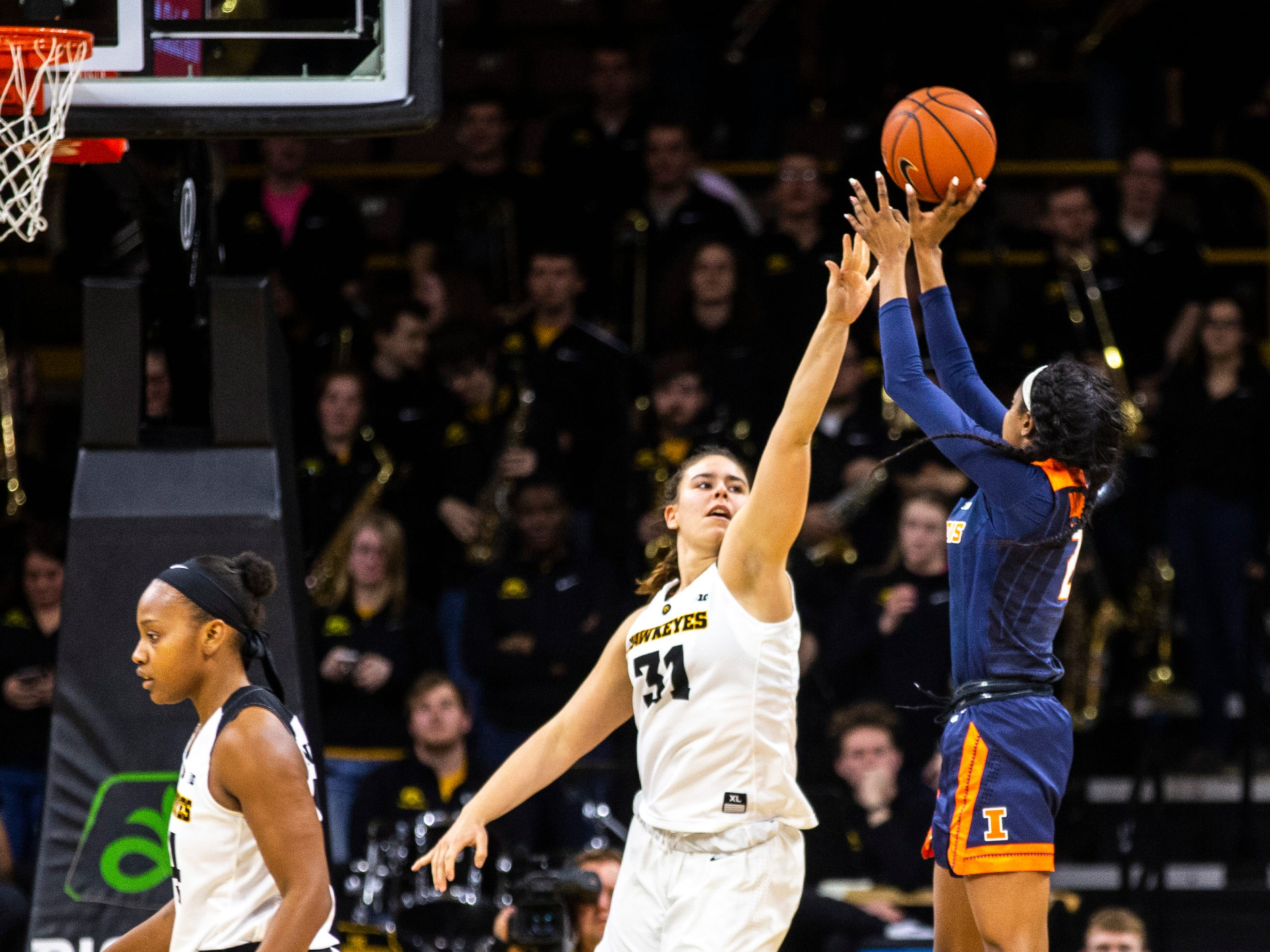 Illinois forward Lyric Robins (2) shoots while Iowa's Paula Valino Ramos (31) defends during a NCAA Big Ten Conference women's basketball game on Thursday, Feb. 14, 2019 at Carver-Hawkeye Arena in Iowa City, Iowa.