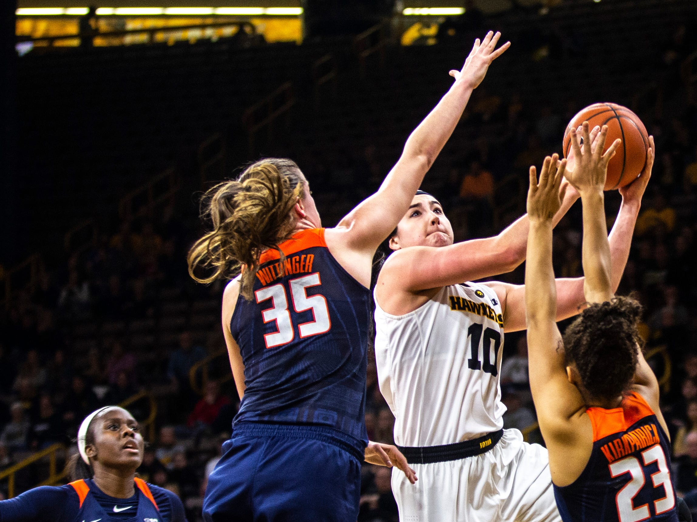 Iowa center Megan Gustafson (10) drives to the basket while Illinois' Cierra Rice, left, Alex Wittinger (35) and Jaelyne Kirkpatrick (23) defend during a NCAA Big Ten Conference women's basketball game on Thursday, Feb. 14, 2019 at Carver-Hawkeye Arena in Iowa City, Iowa.