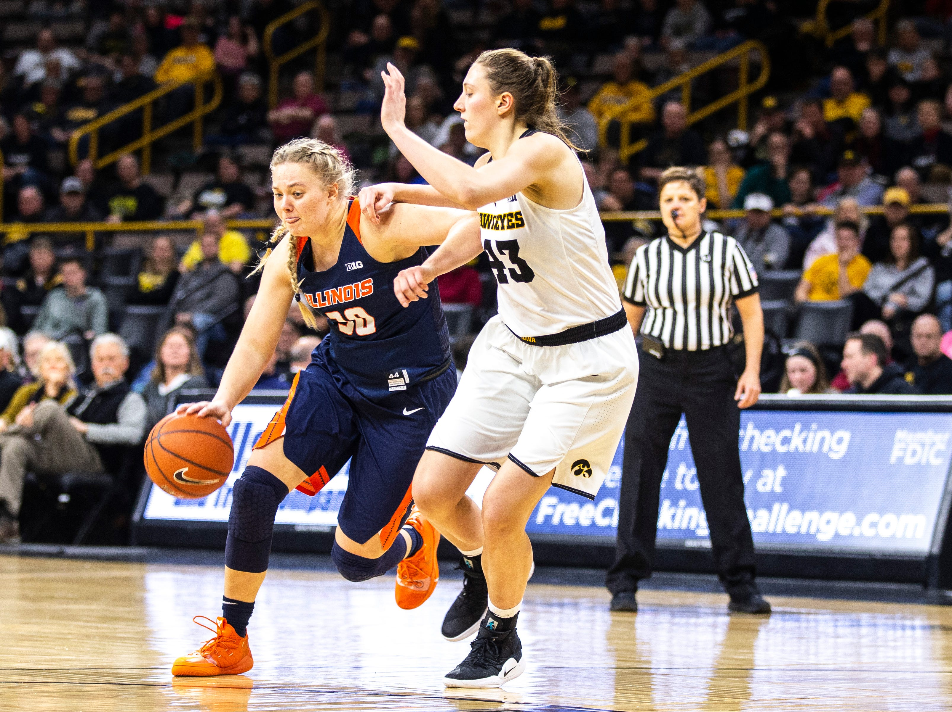 Illinois guard Courtney Joens takes the ball up court while Iowa forward Amanda Ollinger (43) defends during a NCAA Big Ten Conference women's basketball game on Thursday, Feb. 14, 2019 at Carver-Hawkeye Arena in Iowa City, Iowa.