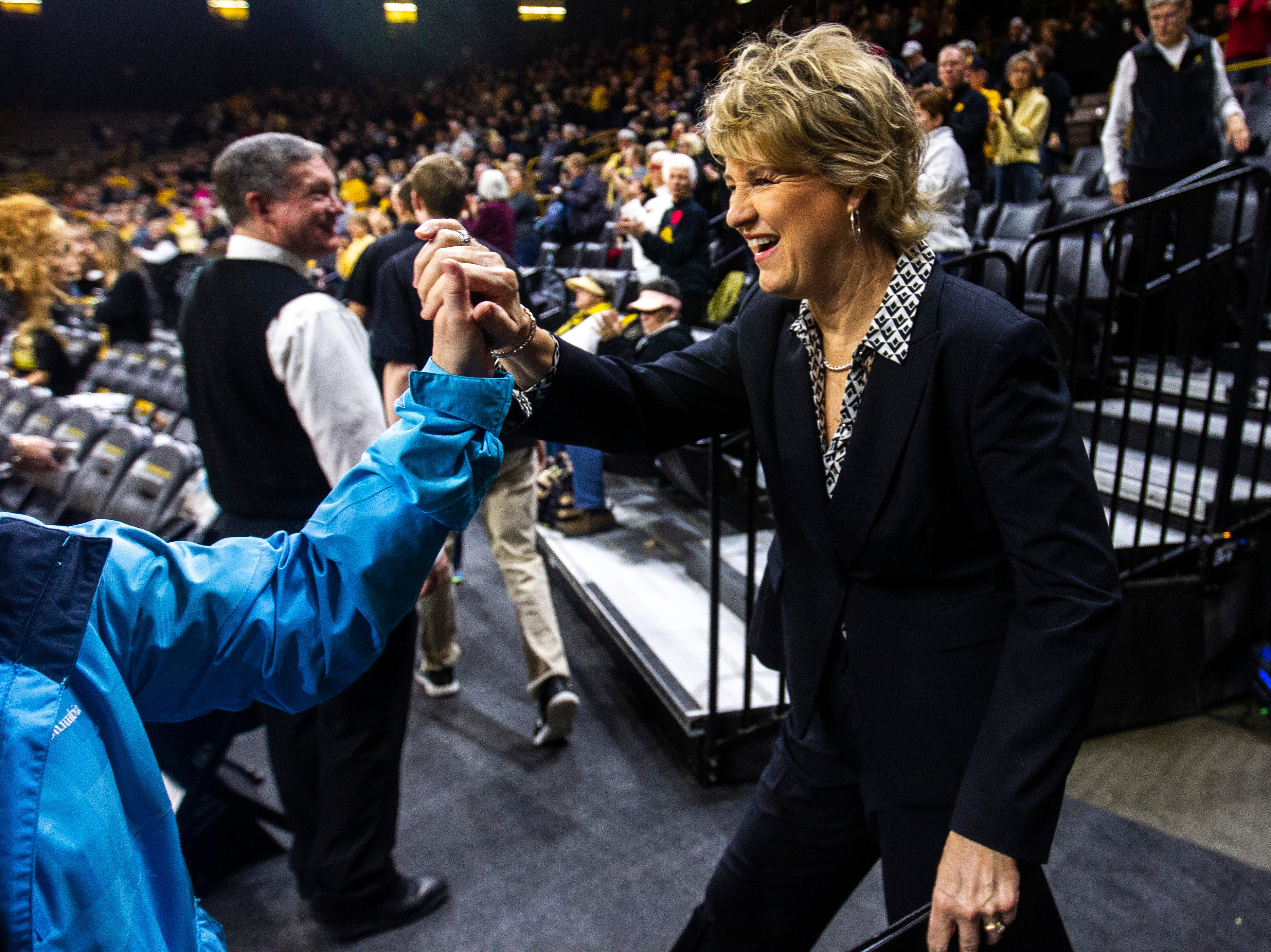 Iowa head coach Lisa Bluder high-fives a fan before a NCAA Big Ten Conference women's basketball game on Thursday, Feb. 14, 2019 at Carver-Hawkeye Arena in Iowa City, Iowa.