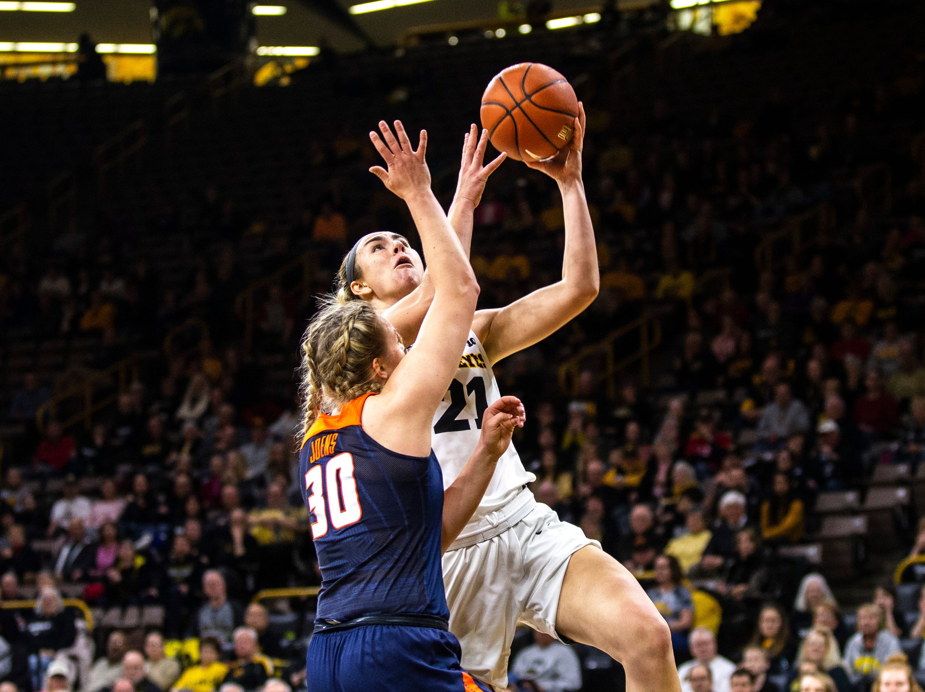 Iowa forward Hannah Stewart (21) drives to the basket while Illinois guard Courtney Joens (30) defends during a NCAA Big Ten Conference women's basketball game on Thursday, Feb. 14, 2019 at Carver-Hawkeye Arena in Iowa City, Iowa.