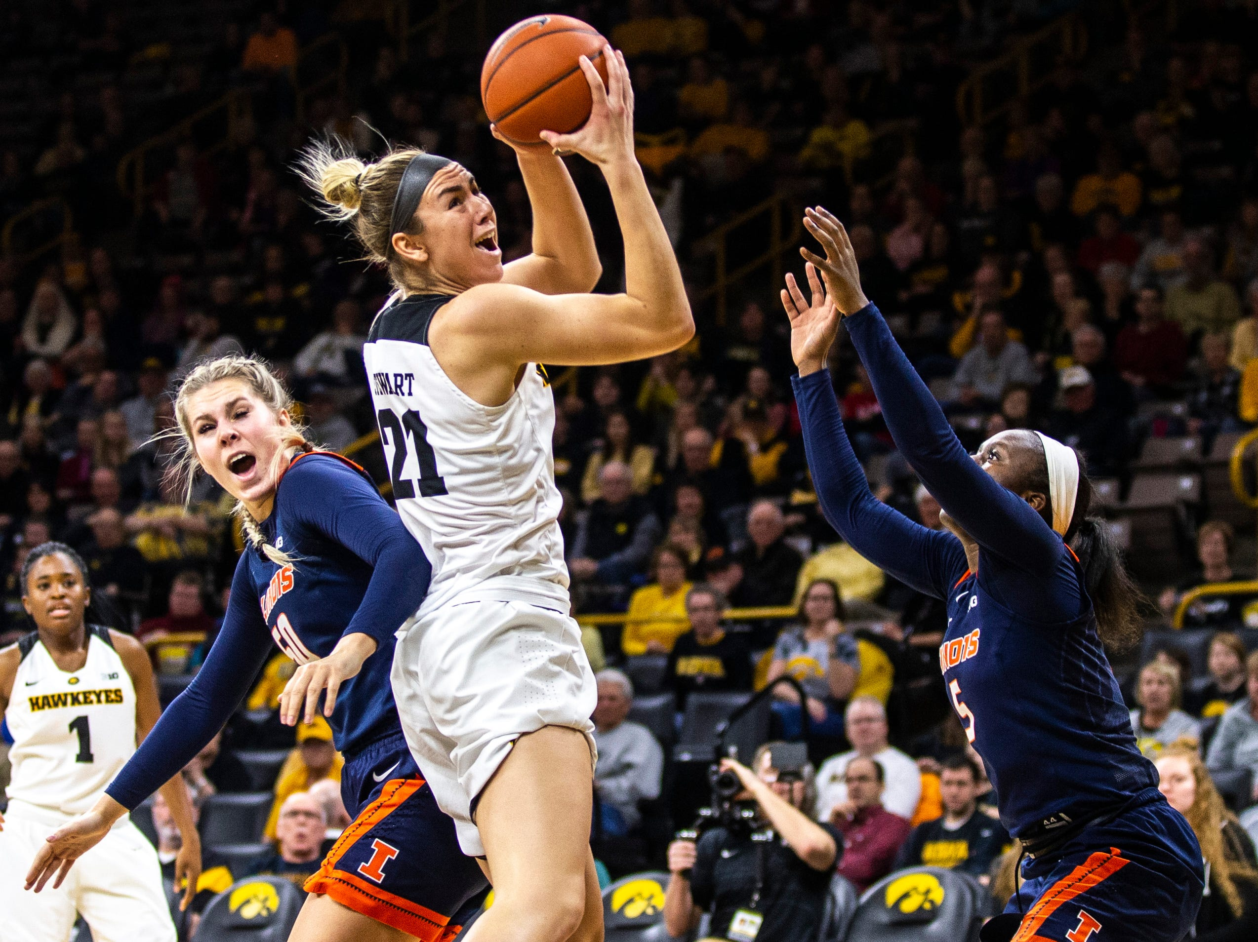 Iowa forward Hannah Stewart (21) goes for a rebound against Illinois forward Ali Andrews, left, and guard Cierra Rice during a NCAA Big Ten Conference women's basketball game on Thursday, Feb. 14, 2019 at Carver-Hawkeye Arena in Iowa City, Iowa.