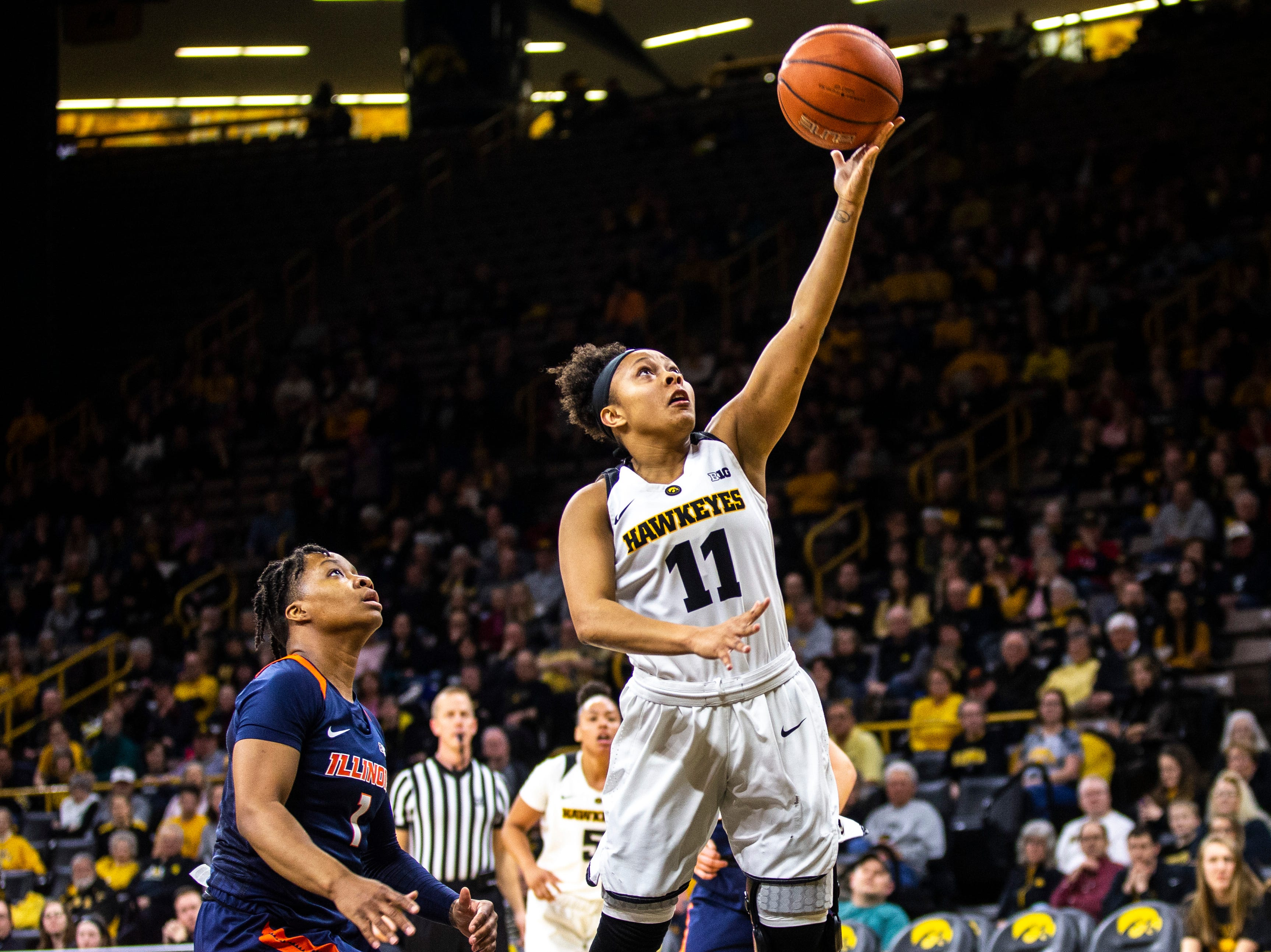 Iowa guard Tania Davis (11) makes a layup while Illinois guard Brandi Beasley defends during a NCAA Big Ten Conference women's basketball game on Thursday, Feb. 14, 2019 at Carver-Hawkeye Arena in Iowa City, Iowa.