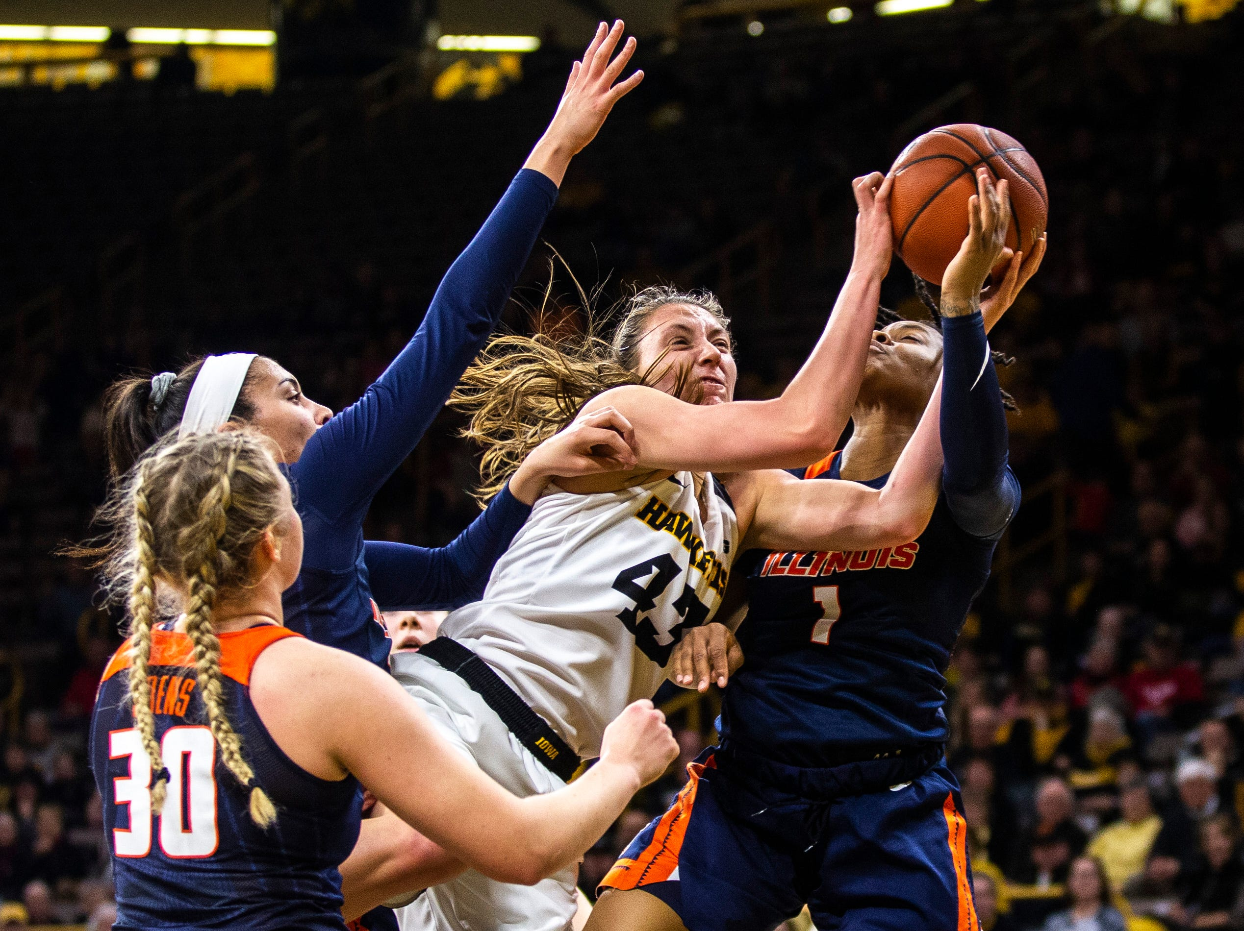 Iowa forward Amanda Ollinger (43) gets tangled up with Illinois' Sarah Shewan, left, and Brandi Beasley (1) while  Courtney Joens (30) defends during a NCAA Big Ten Conference women's basketball game on Thursday, Feb. 14, 2019 at Carver-Hawkeye Arena in Iowa City, Iowa.
