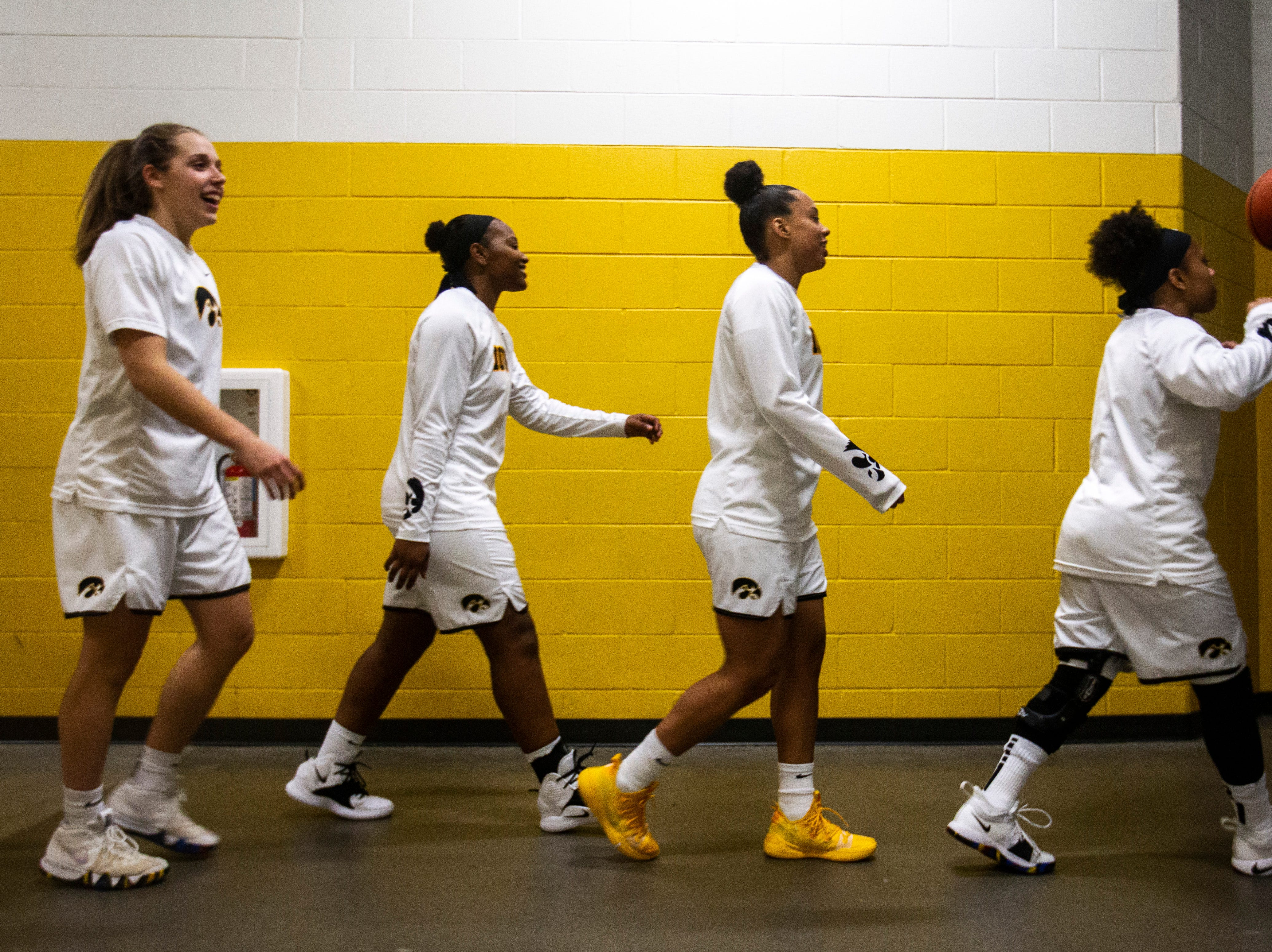 Iowa Hawkeyes Tania Davis (from right), Alexis Sevillian, Zion Sanders and Kathleen Doyle run out towards the court during a NCAA Big Ten Conference women's basketball game on Thursday, Feb. 14, 2019 at Carver-Hawkeye Arena in Iowa City, Iowa.
