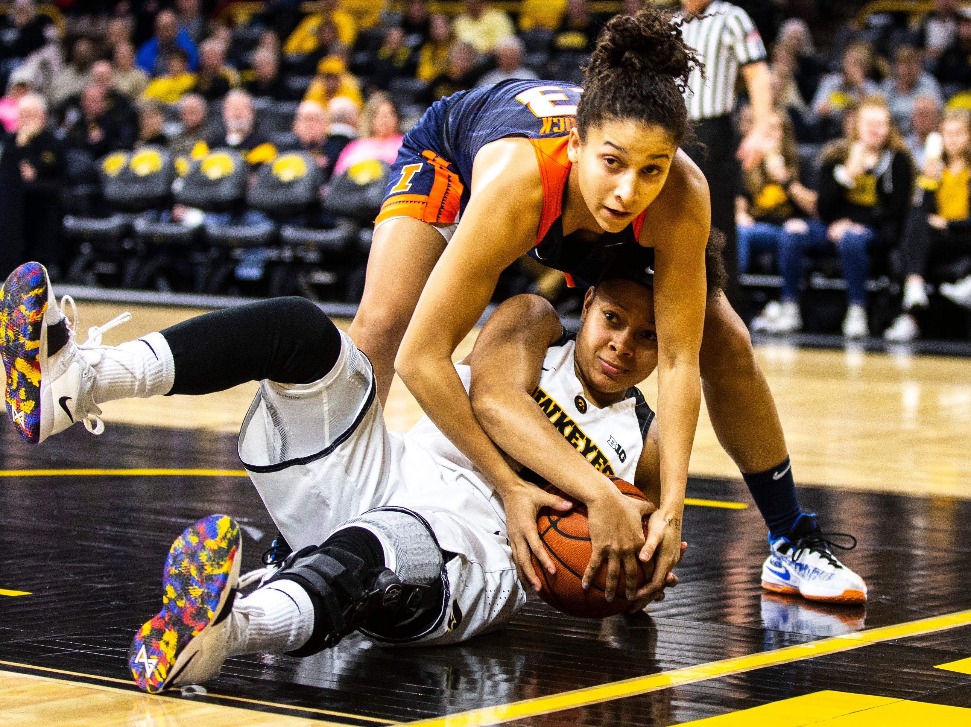 Iowa guard Tania Davis (11) and Illinois guard Jaelyne Kirkpatrick (23) battle for a jump ball during a NCAA Big Ten Conference women's basketball game on Thursday, Feb. 14, 2019 at Carver-Hawkeye Arena in Iowa City, Iowa.