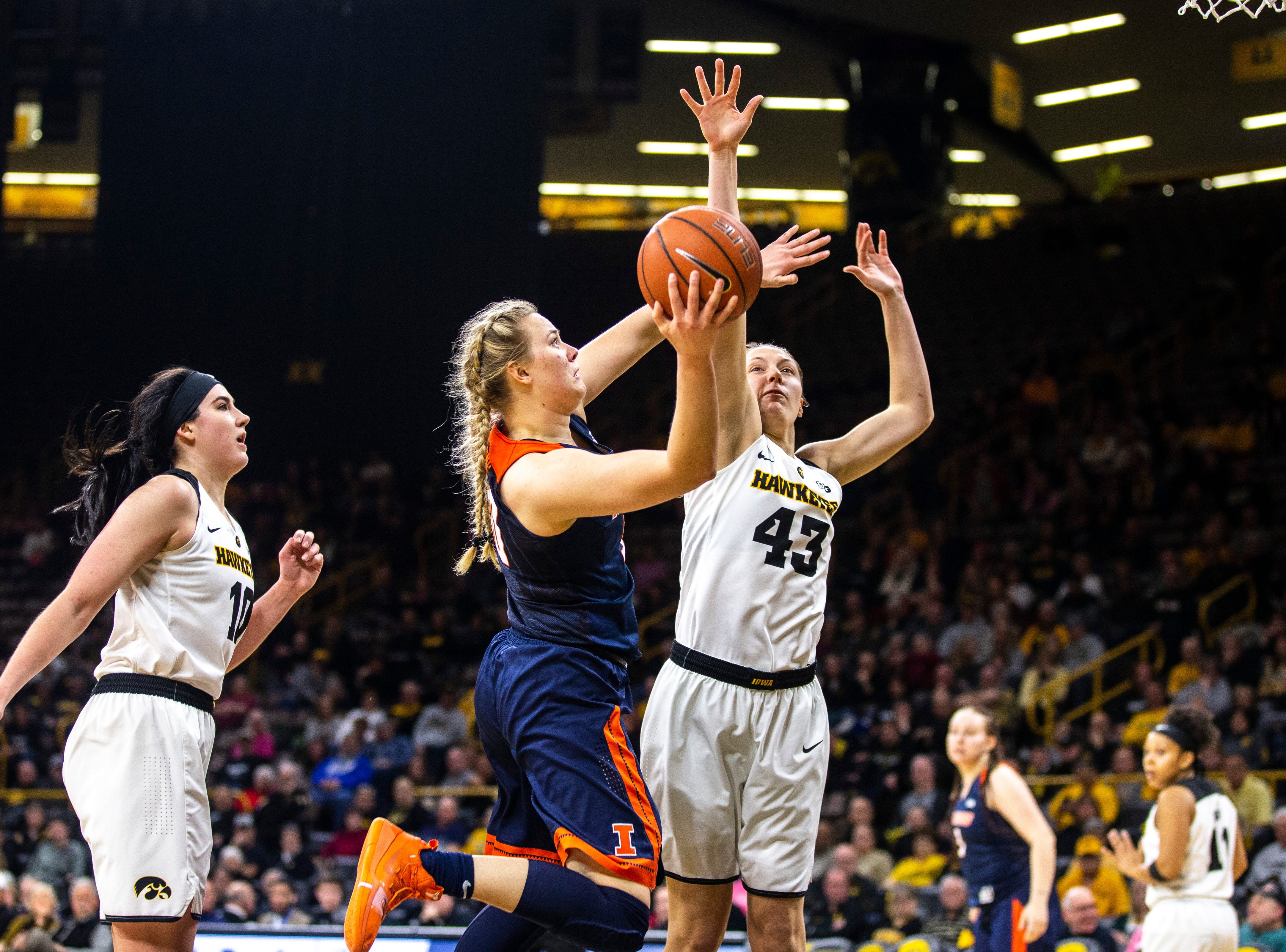Illinois guard Courtney Joens drives to the basket while Iowa center Megan Gustafson, left, and Iowa forward Amanda Ollinger (43) defend during a NCAA Big Ten Conference women's basketball game on Thursday, Feb. 14, 2019 at Carver-Hawkeye Arena in Iowa City, Iowa.