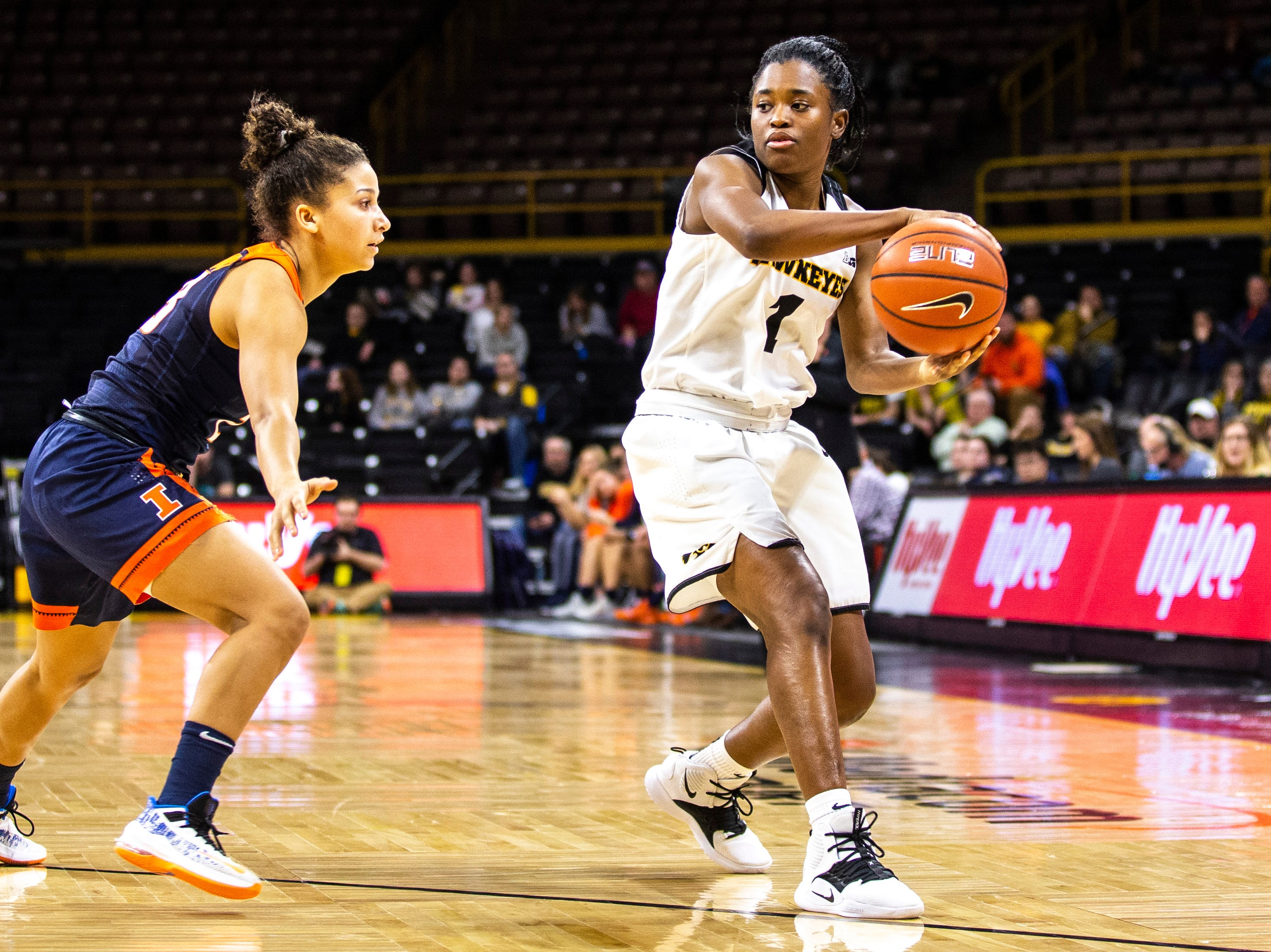 Iowa guard Tomi Taiwo (1) passes to teammate while Illinois guard Jaelyne Kirkpatrick, left, defends during a NCAA Big Ten Conference women's basketball game on Thursday, Feb. 14, 2019 at Carver-Hawkeye Arena in Iowa City, Iowa.