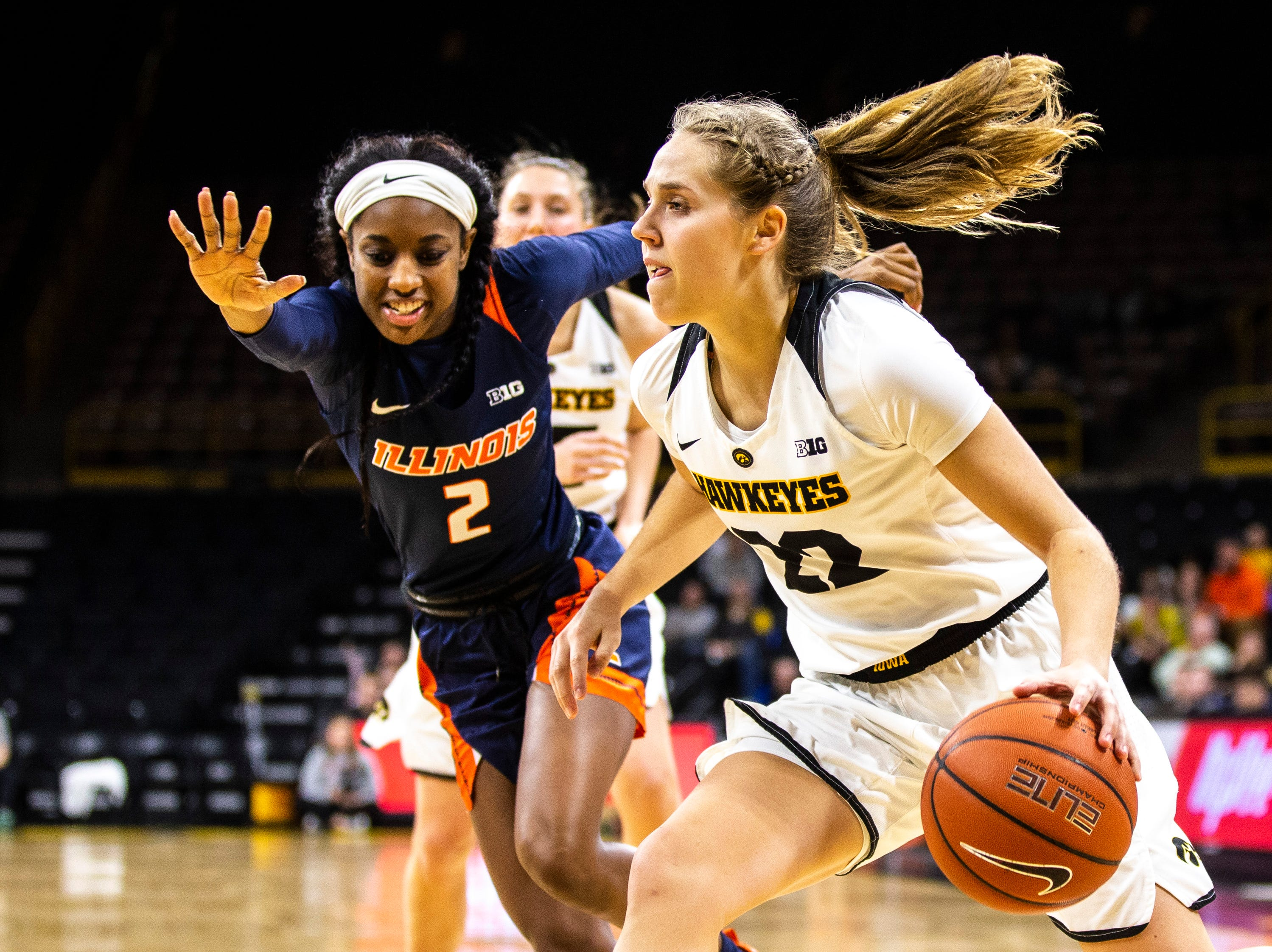 Iowa guard Kathleen Doyle (22) drives to the basket while Illinois forward Lyric Robins (2) defends during a NCAA Big Ten Conference women's basketball game on Thursday, Feb. 14, 2019 at Carver-Hawkeye Arena in Iowa City, Iowa.