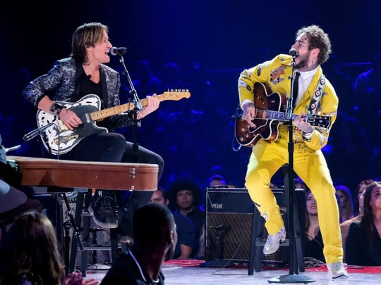 "Post Malone, right, wears a suit made by Jerry Lee Atwood while performing with Keith Urban on the ""Elvis All-Star Tribute"" special airing Sunday, Feb. 17, on NBC."