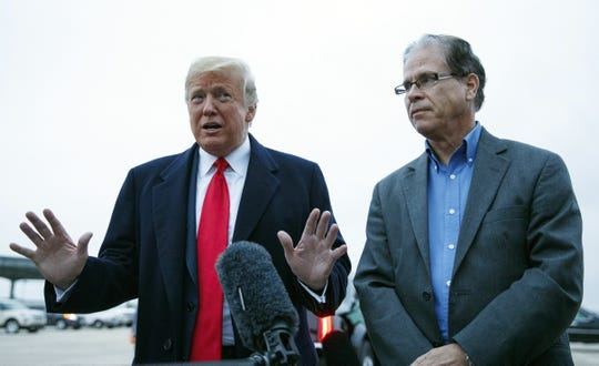 President Donald Trump stands with Mike Braun, who is running to unseat Democratic Sen. Joe Donnelly, as he talks with the media as he arrives on Air Force One, Monday, Nov. 5, 2018, at Fort Wayne International Airport, in Fort Wayne, Ind., en route to Allen County War Memorial Coliseum for a rally.