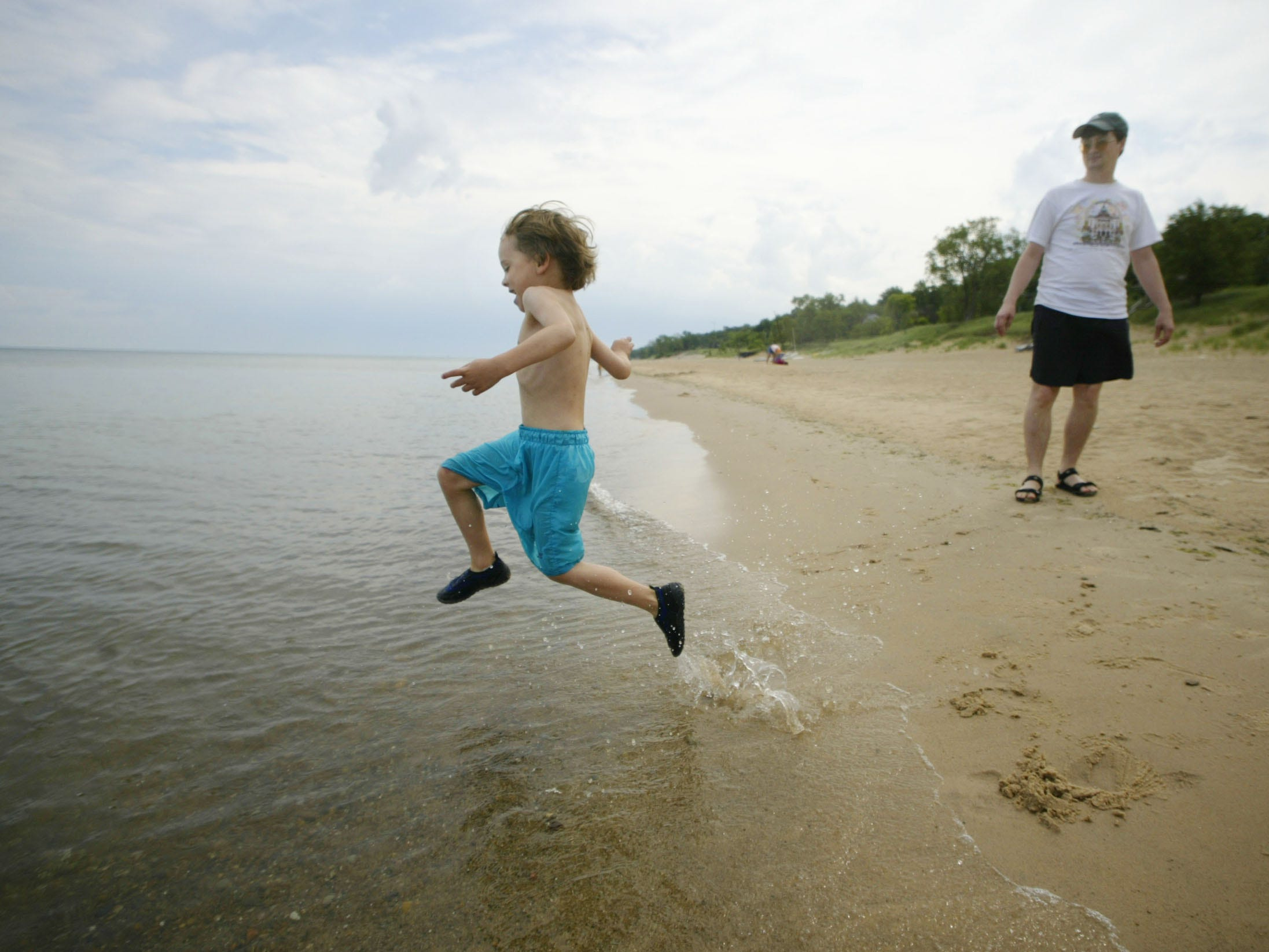 Joe Eagle, 5, of Homewood, Illinois, leaps into Lake Michigan at Lakeview Beach near Beverly Shores, Indiana, as his father Jay looks on.