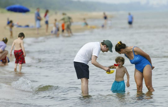 Joe Eagle, 5, of Homewood, Illinois, is framed by dad Jay left and mom Amy as the trio visit Lake Michigan at Lakeview Beach near Beverly Shores, Indiana.