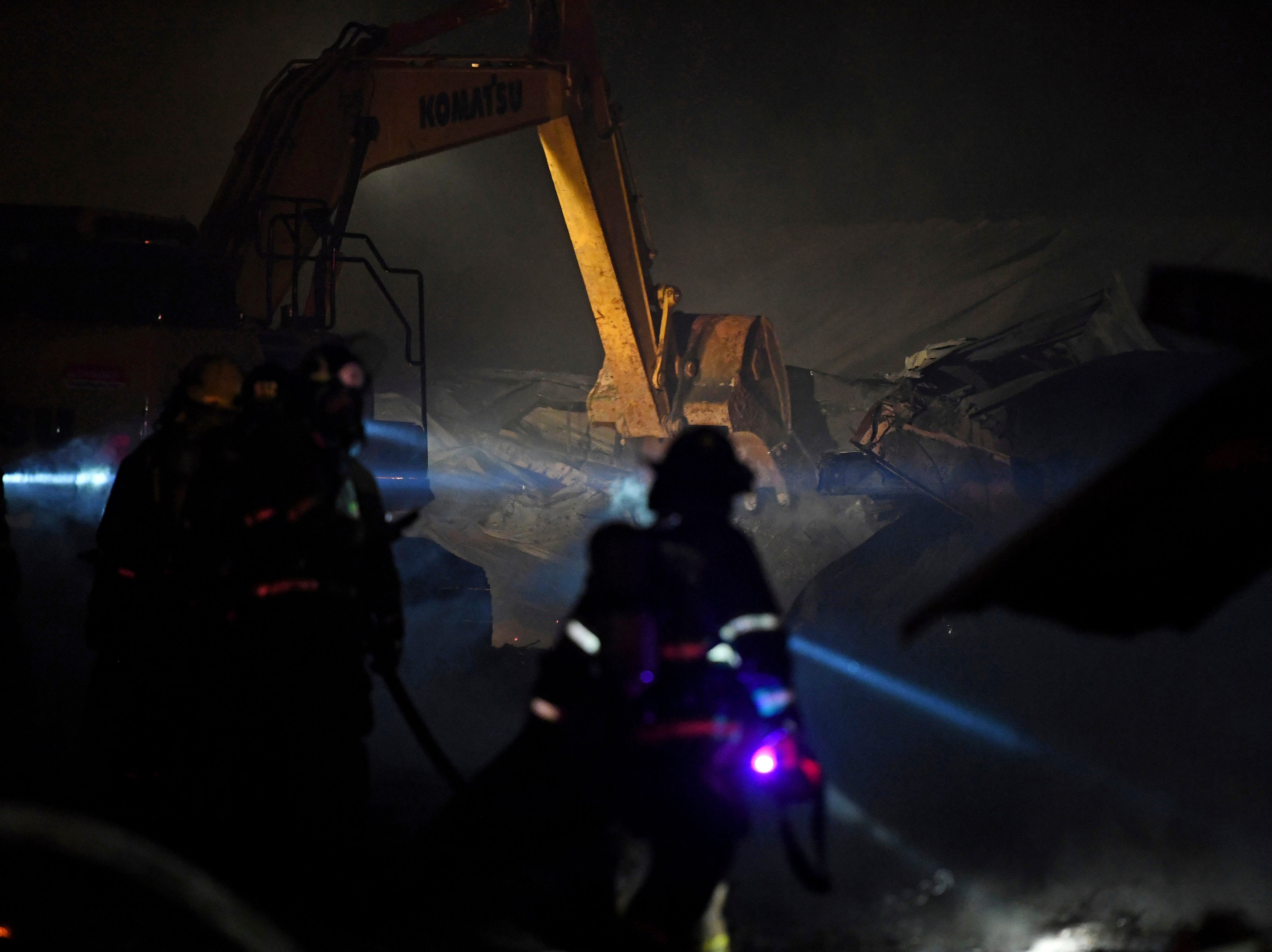 Firefighters use an excavator to find hotspots while extinguishing a fire at American Furniture Manufacturing in Ecru, Miss., Thursday, Feb. 14, 2019. The fire was the third fire at the facility in just over one year and is still under investigation.