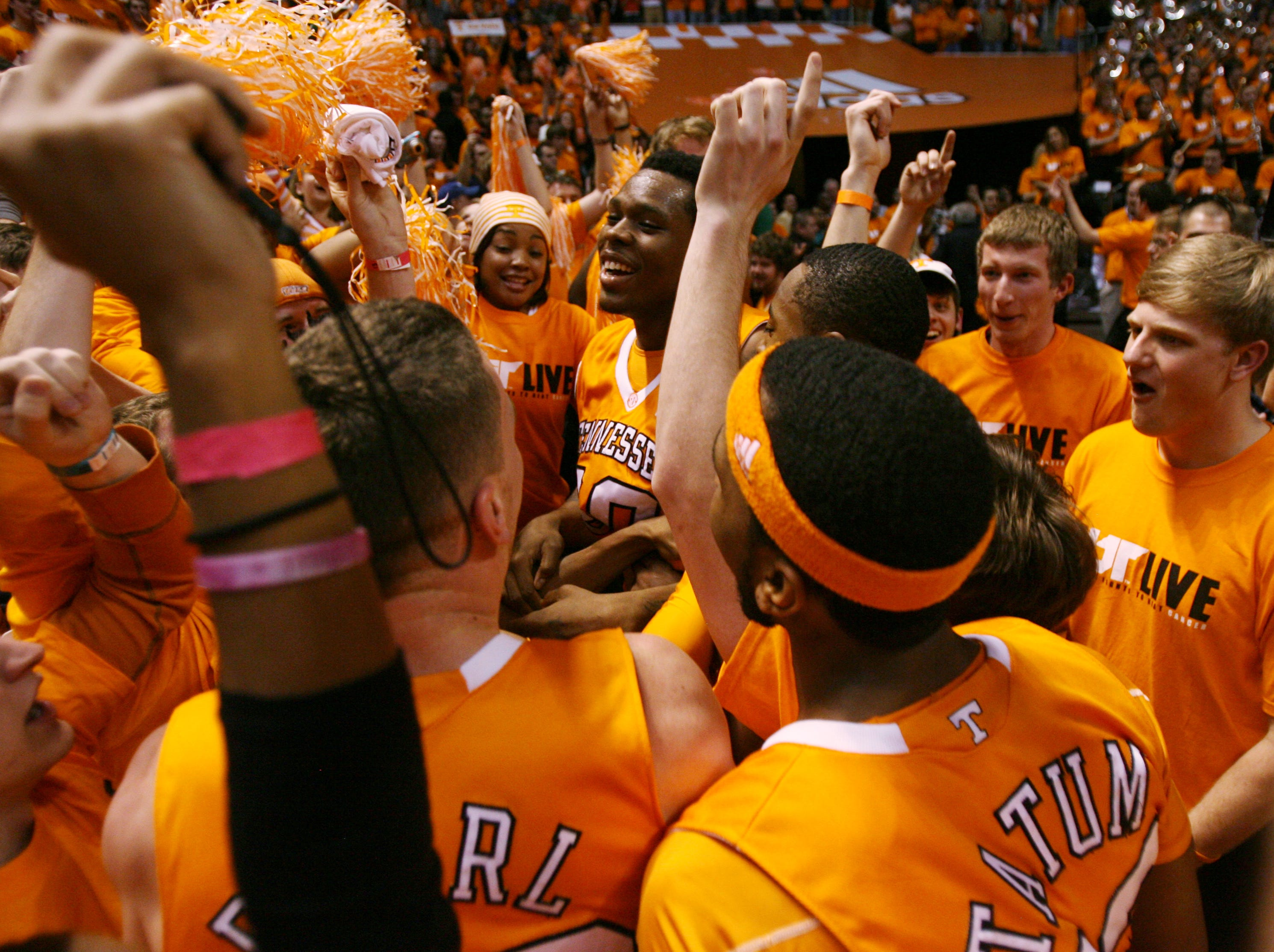 Tennessee's Kenny Hall, center, and teammates celebrate with Vol fans after they defeated the Kentucky Wildcats 74-65 at Thompson-Boling Arena Saturday, Feb. 27, 2010.