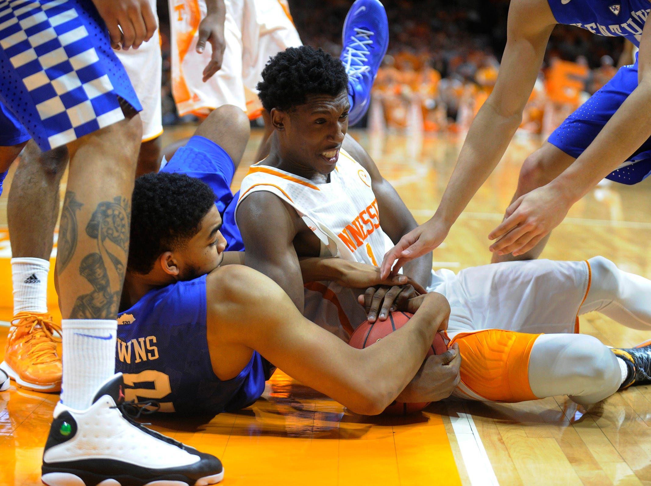 Tennessee guard Josh Richardson (1) fights for the ball against Kentucky forward Karl-Anthony Towns (12) during the second half at Thompson-Boling Arena in Knoxville on Tuesday, Feb. 17, 2015. Kentucky defeated Tennessee 66-48.