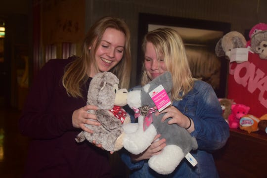 Madison Harvey and Kelsie Hall can't help but play with the stuffed animals collected during a toy drive to benefit sick kids at East Tennessee Children's Hospital.