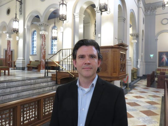 Glenn Kahler, director of music and liturgy at Sacred Heart Cathedral, stands in the front of the nave of the church.