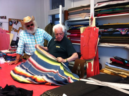 Phil Rupp and Manuel, country music's premiere couturier, examine some fabric in the octogenarian designer's Nashville shop. June 26, 2013
