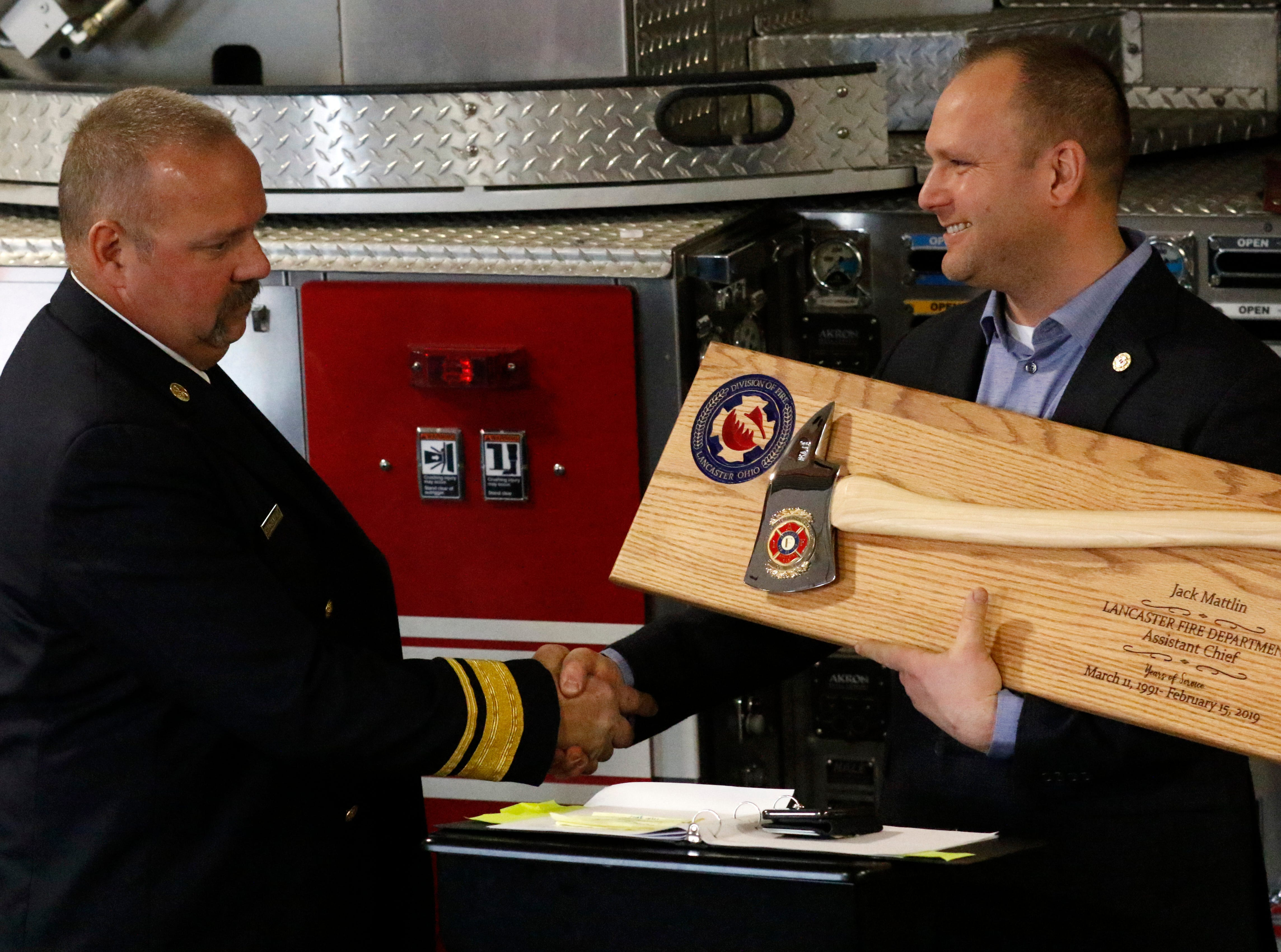 Assistant Chief Jack Mattlin, left, shakes hands Pete Anson, president of the International Association of Firefighters, Local 291 union, Friday afternoon, Feb. 15, 2019, at Engine House One in Lancaster. Mattlin retired from the fire department after 28 years.