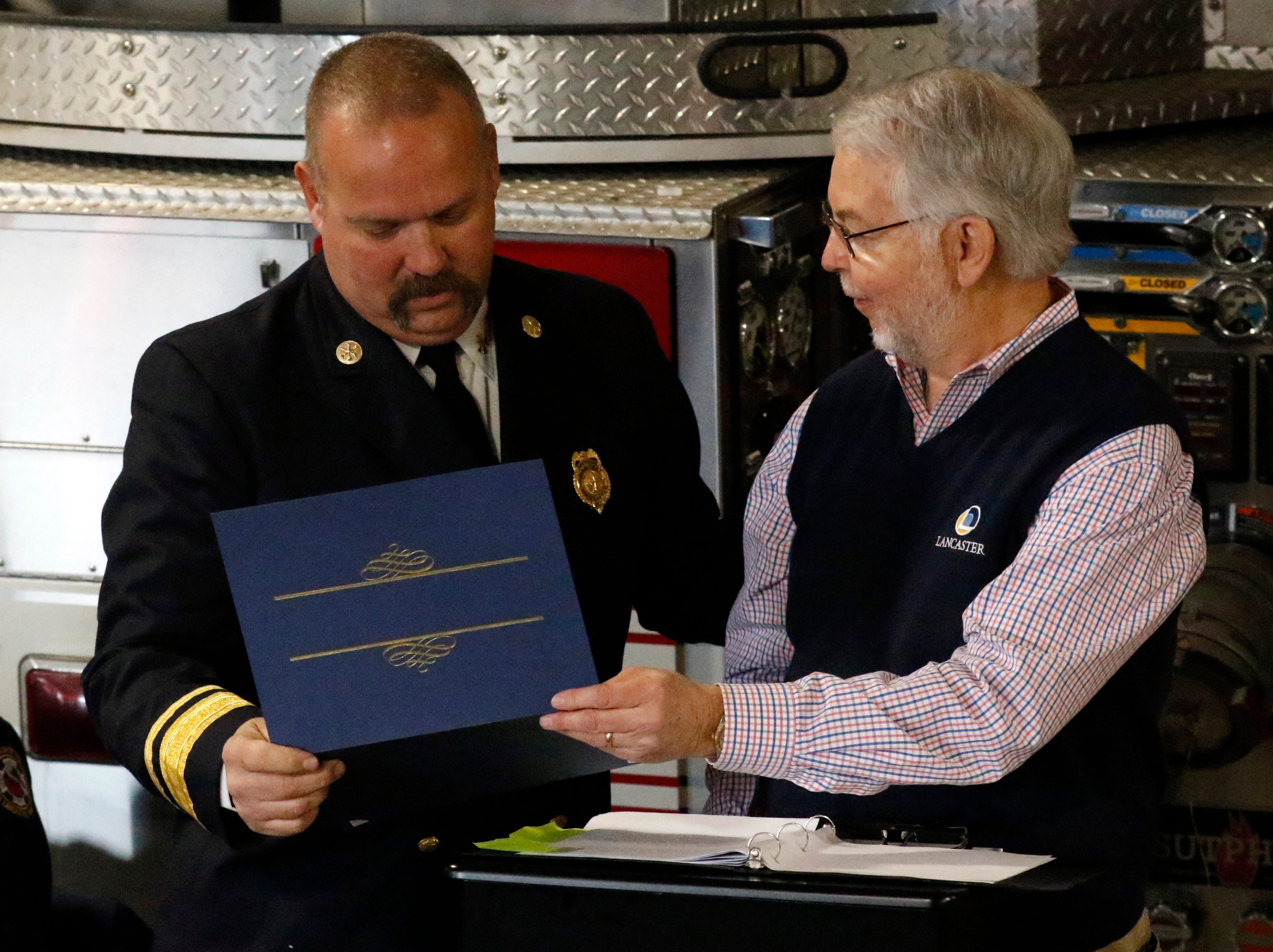 Lancaster Mayor David Scheffler, right hands retiring Lancaster Assistant Fire Chief Jack Mattlin a commendation at a retirement and promotion ceremony Friday afternoon, Feb. 15, 2019, at Engine House One in Lancaster. Mattlin retired after 28 years with the department.