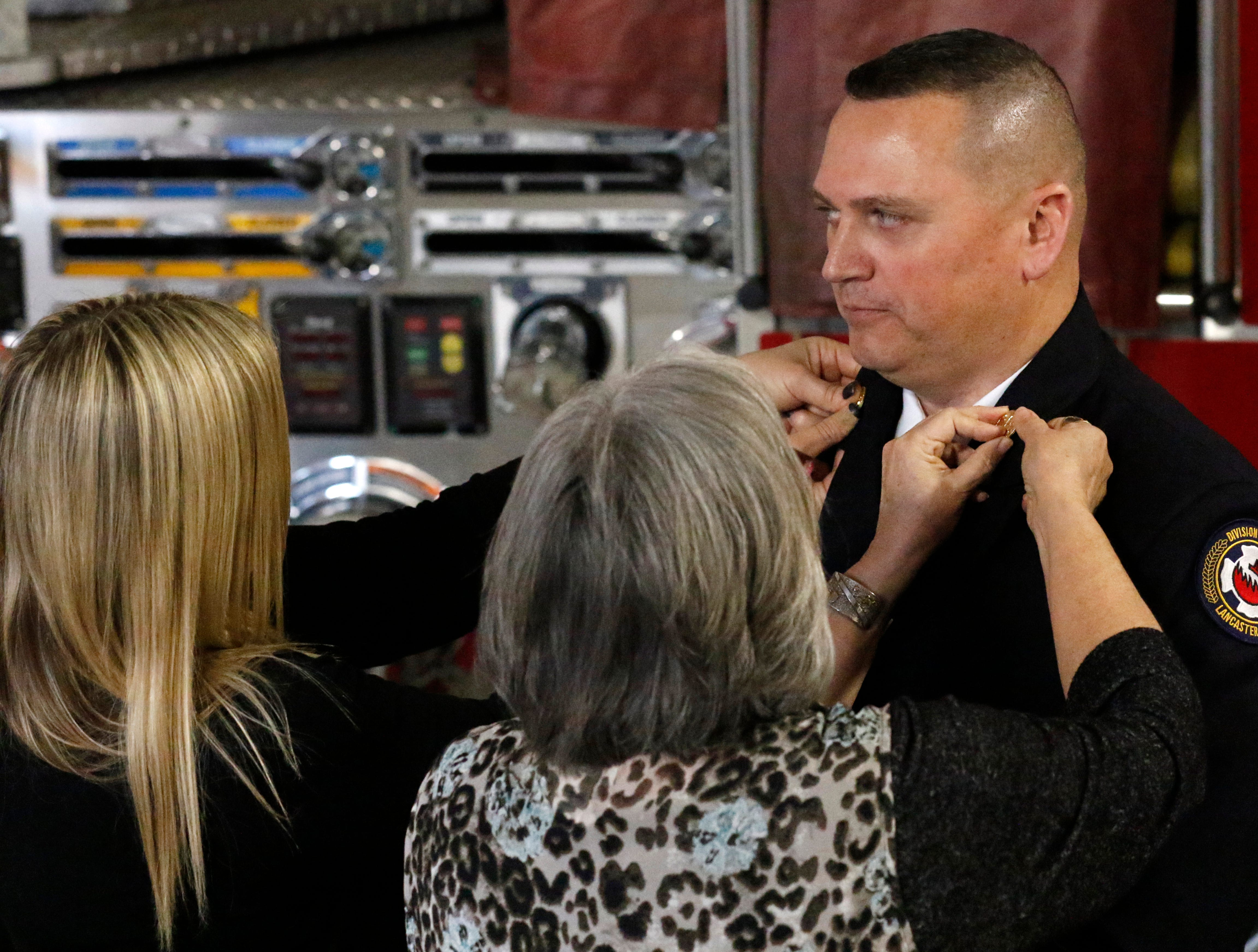 Family members pin Assistant Chief K.J. Watts' new rank insignia to his uniform jacket Friday afternoon, Feb. 15, 2019, at Engine House One in Lancaster.