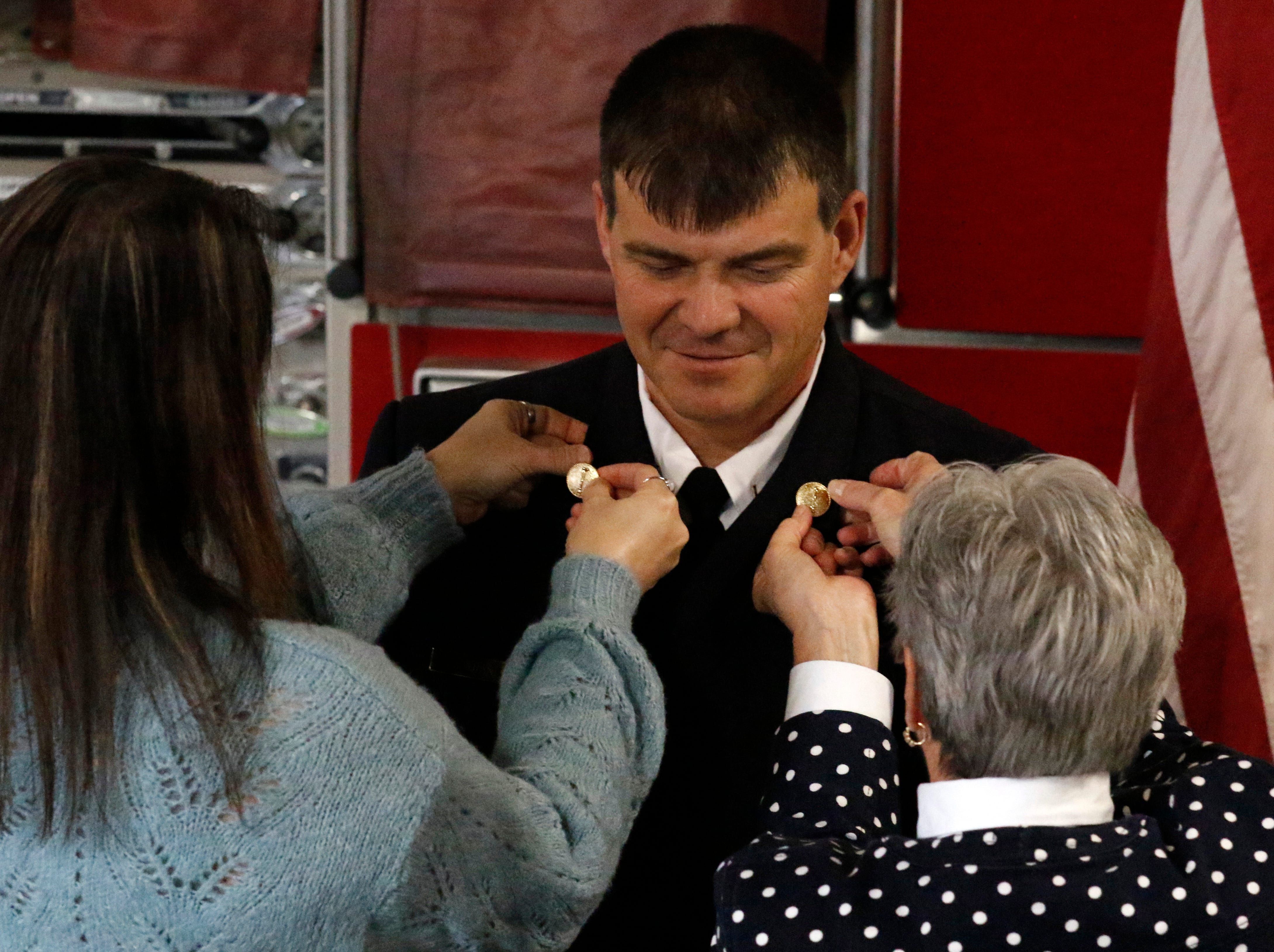 Family members pin Lt. Jeremy Kraner's new rank insignia to his uniform jacket Friday afternoon, Feb. 15, 2019, at Engine House One in Lancaster.