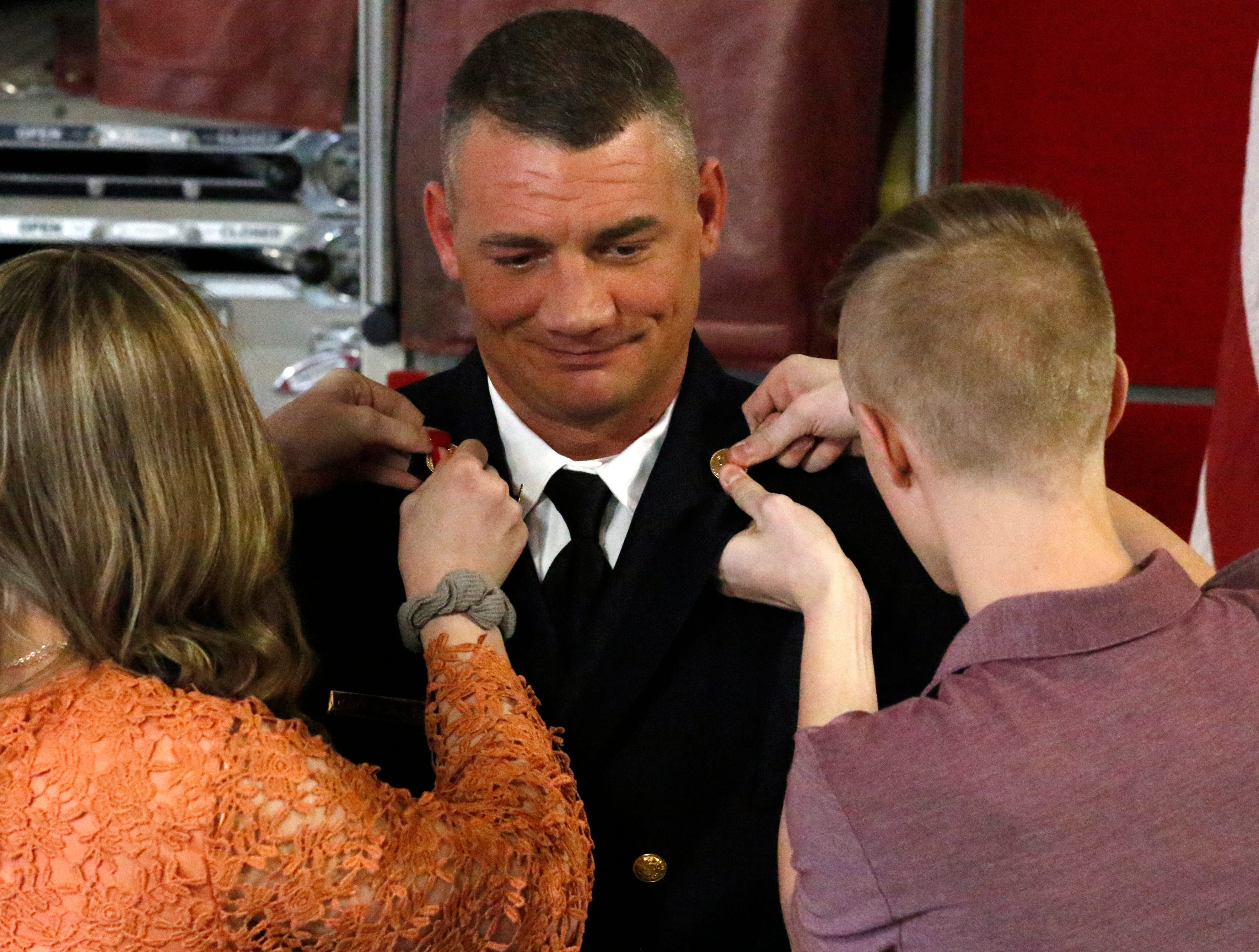 Family members pin Capt. Slade Schultz new rank insignia to his uniform jacket Friday afternoon, Feb. 15, 2019, at Engine House One in Lancaster.