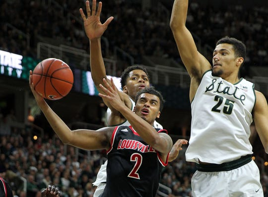 Dec 2, 2015; East Lansing, MI, USA; Louisville Cardinals guard Quentin Snider (2) is defended by Michigan State Spartans forward Kenny Goins (25) and Michigan State Spartans forward Deyonta Davis (23) during the 1st half of a game at Jack Breslin Student Events Center. Mandatory Credit: Mike Carter-USA TODAY Sports