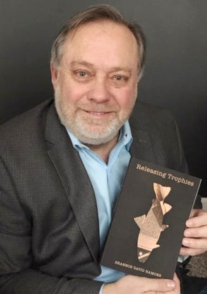 """Shannon David Hamons holds his new book, """"Releasing Trophies."""""""