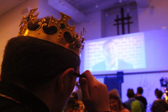 """A crown sits on Presden's head as Tim Tebow declares the crowd """"King and Queens."""""""
