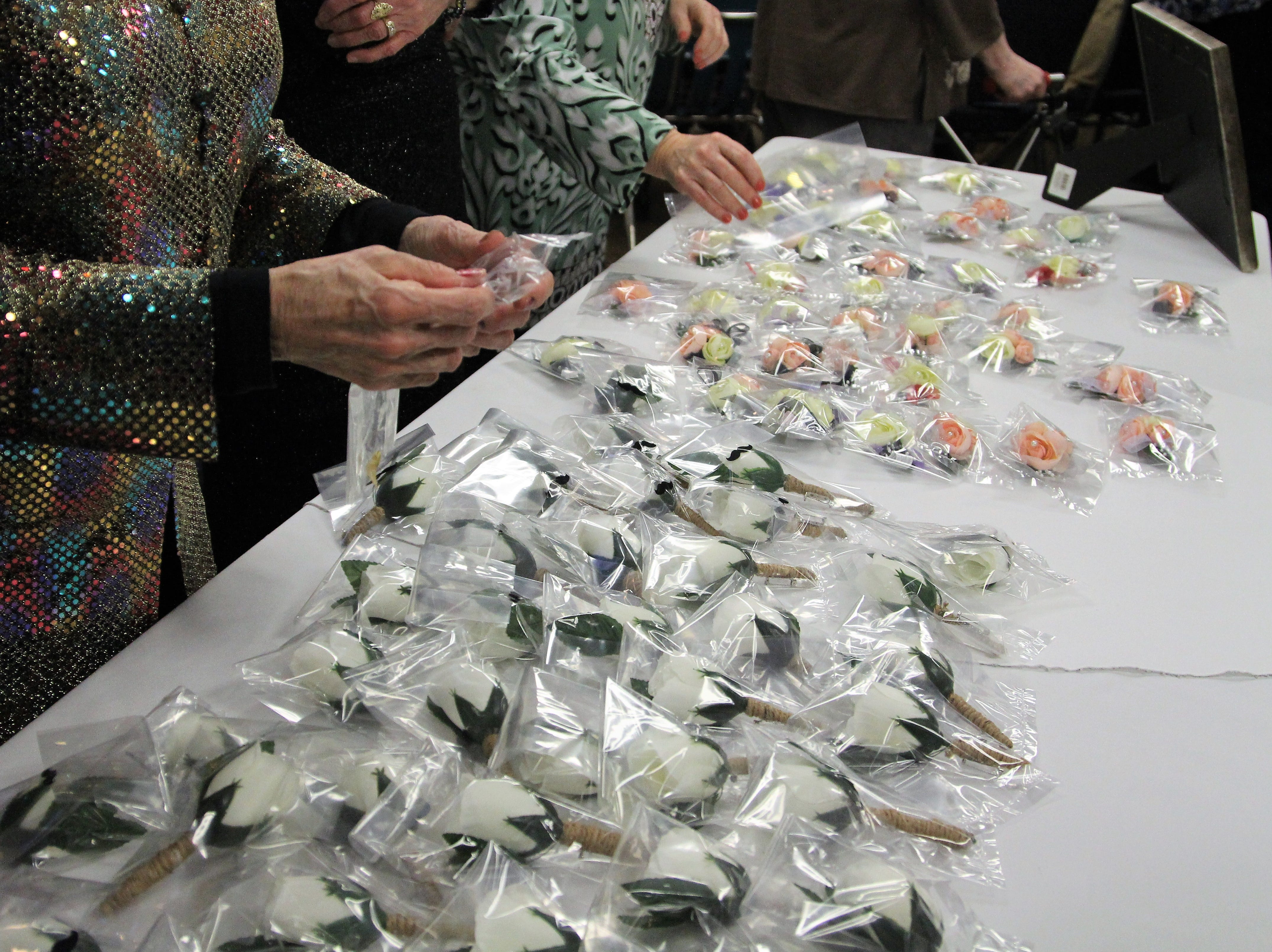 corsages lined a table at Marion First Church of the Nazarene Friday, Feb. 8. Over 300 volunteerswalked around the church, checked guest in, shined shoes, applied make-up and handed out corsages.