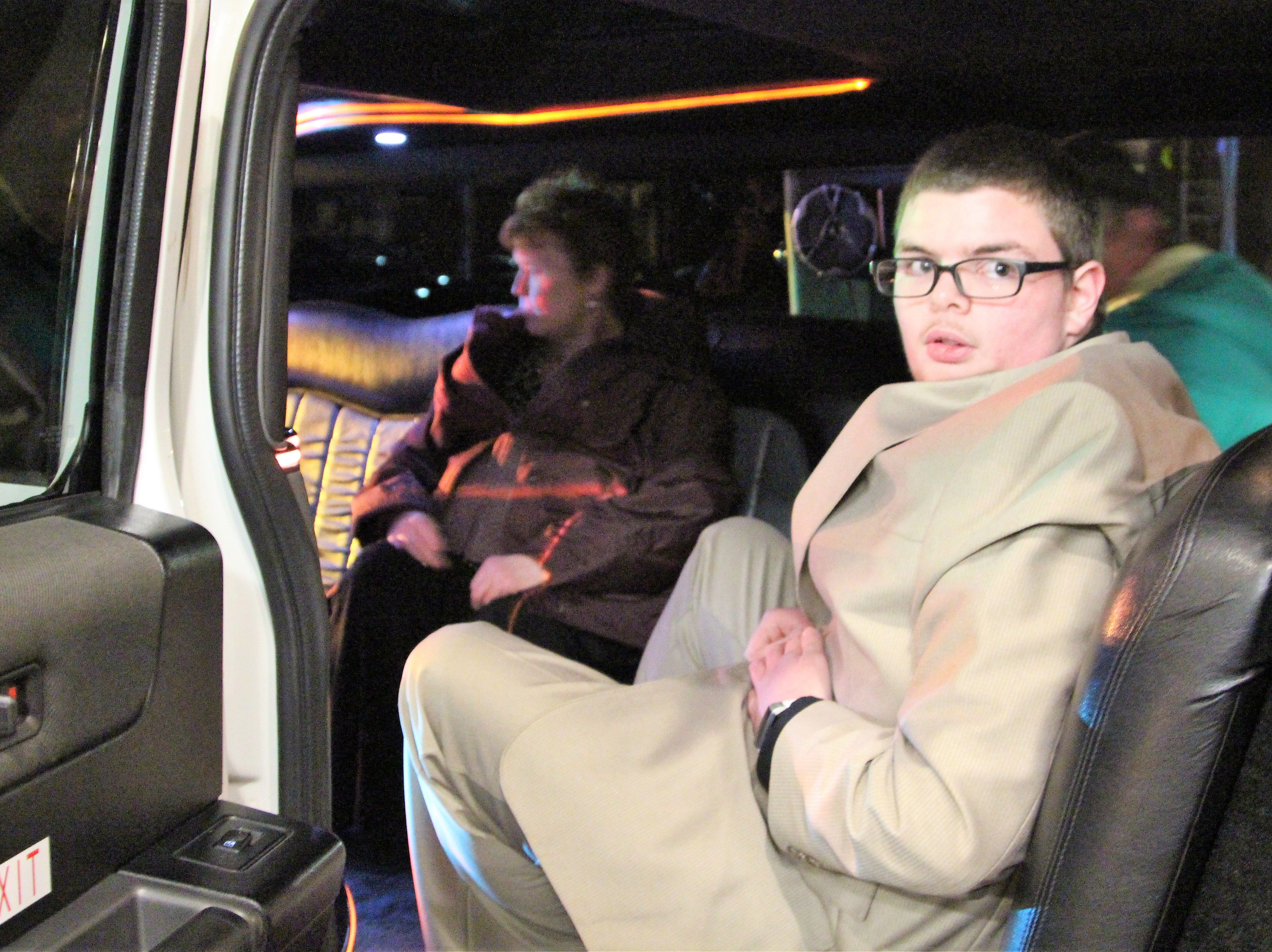 """Presden Deal, a Elgin High School senior, sits inside a limousine. He was driven up to a red carpet where he was met by volunteer """"paparazzi."""""""