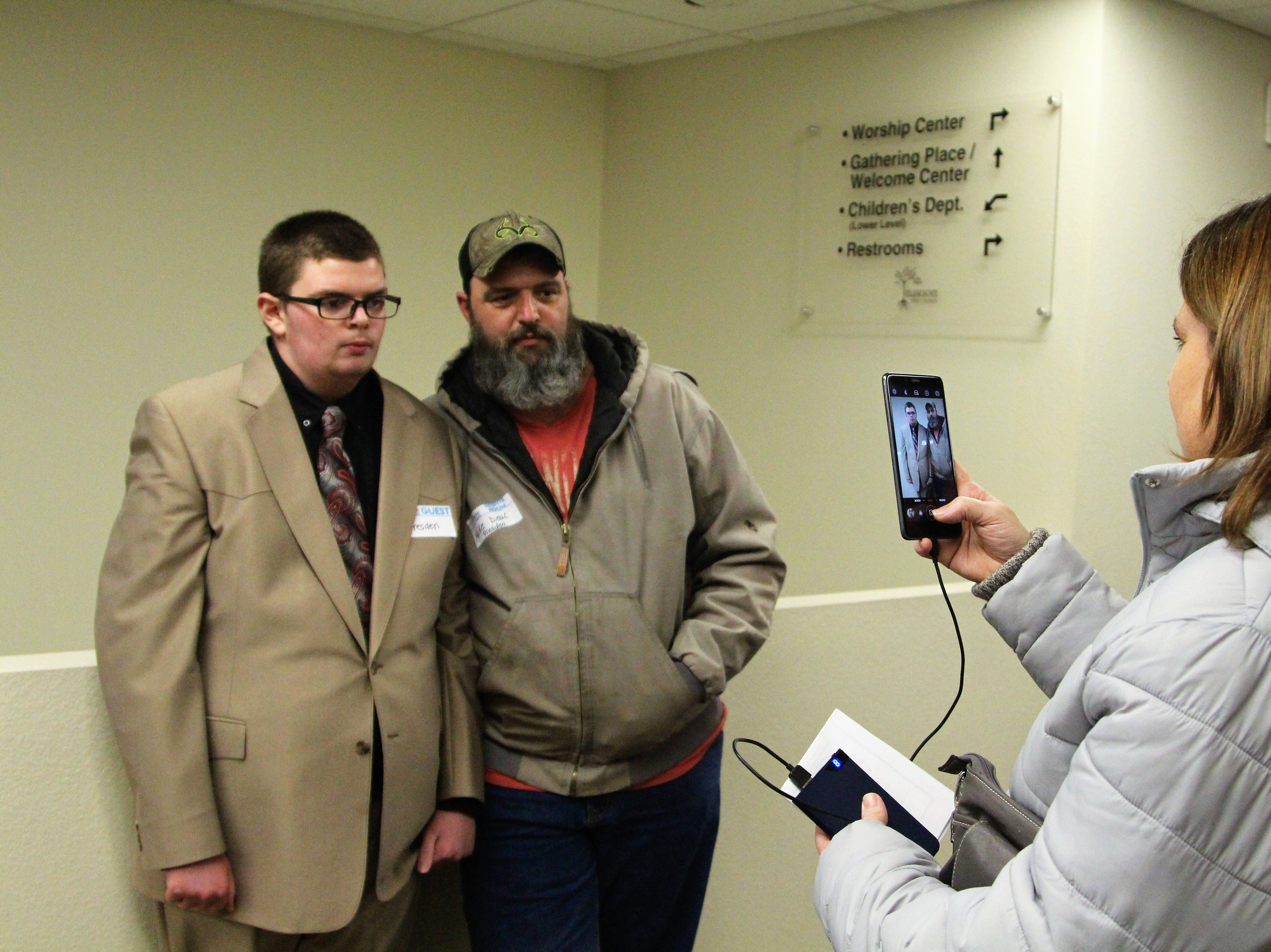 """Wenetta Deal takes a picture of her son Presden and husband Mike as they stand near the entrance of Marion First Church of the Nazarene, which hosted a Night to Shine. """"(Presden) was so little for so long,"""" she recalled. """"Then he got so big. Hasn't slowed down since."""""""