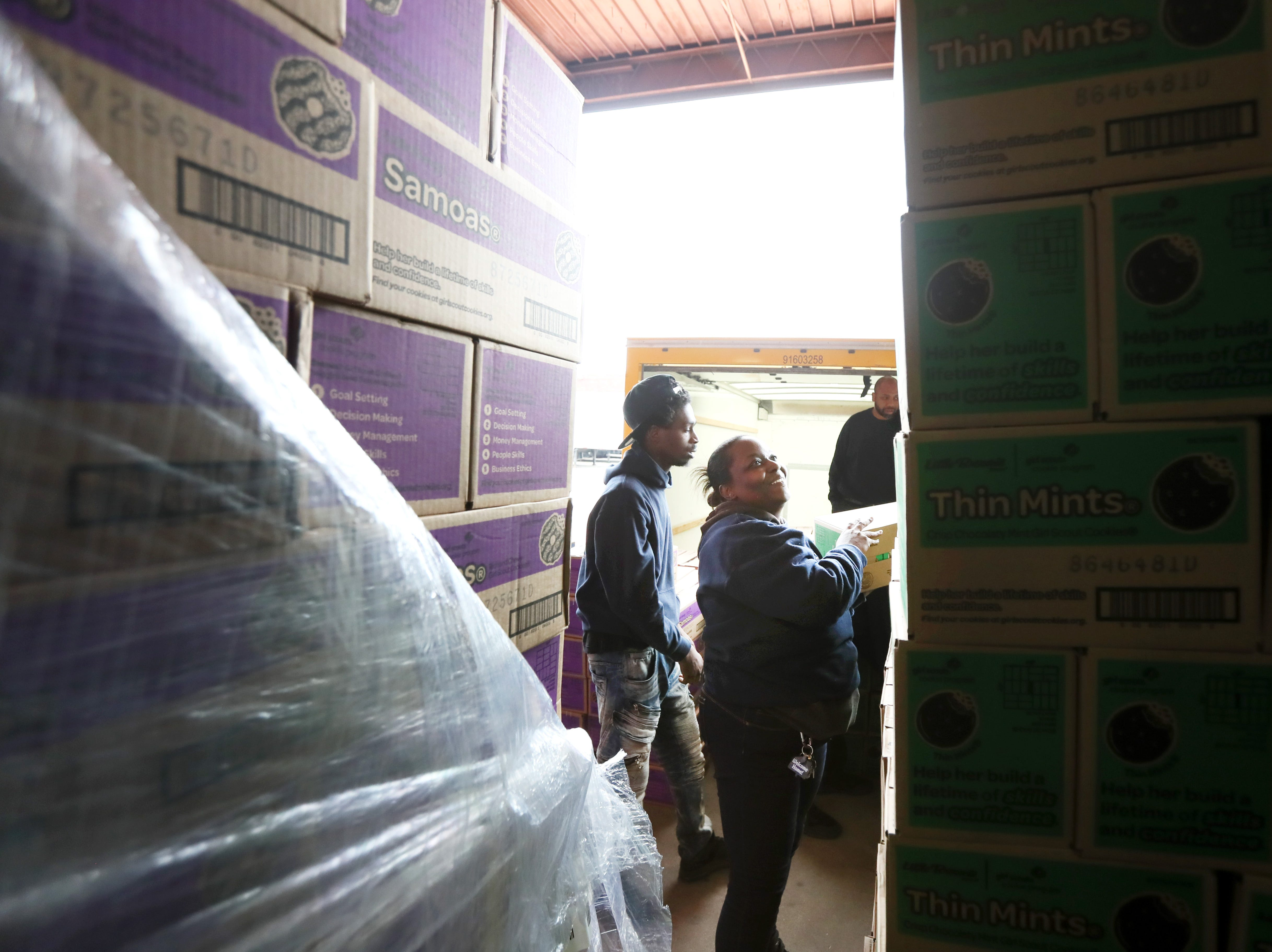 """Kelly Scott works to stack boxes during the Girl Scout Cookie """"Count N' Go"""" distribution at Armstrong Relocation, where they are unloading nearly 77,000 cases of the famed cookie boxes Friday, Feb. 15, 2019."""