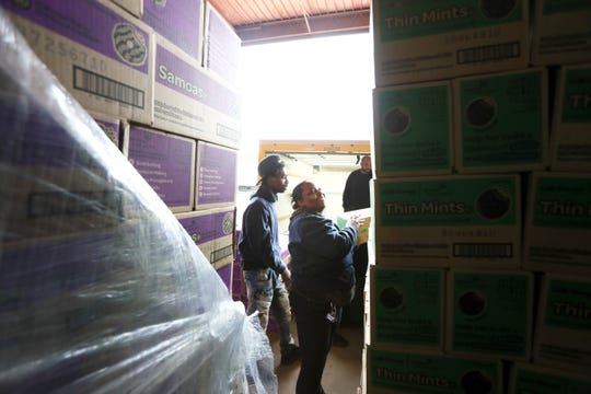 "Kelly Scott works to stack boxes during the Girl Scout Cookie ""Count N' Go"" distribution at Armstrong Relocation, where they are unloading nearly 77,000 cases of the famed cookie boxes Friday, Feb. 15, 2019."