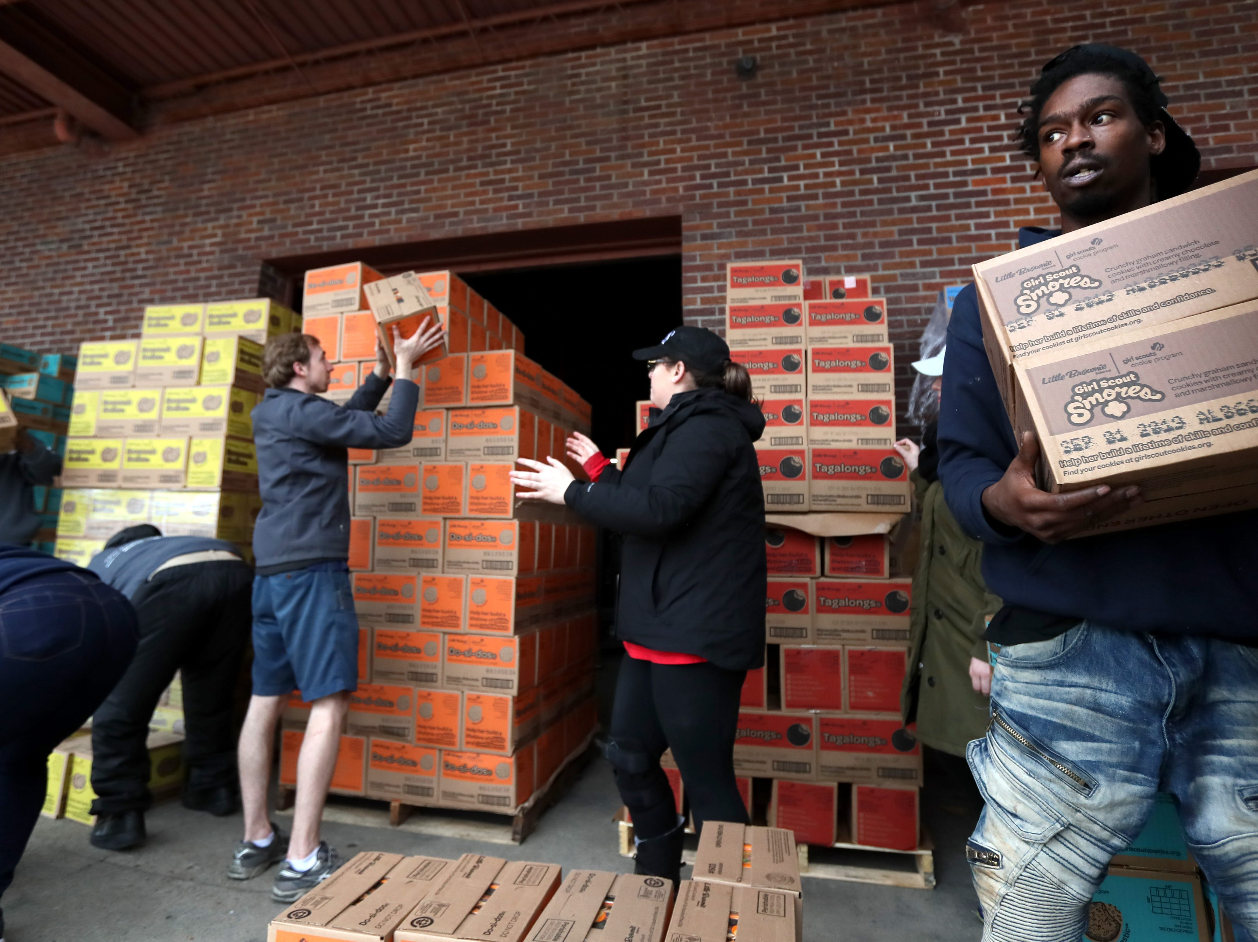 """Kenneth Conly works to load boxes at the Girl Scout Cookie """"Count N' Go"""" distribution at Armstrong Relocation where they are unloading nearly 77,000 cases of the famed cookie boxes Friday, Feb. 15, 2019."""