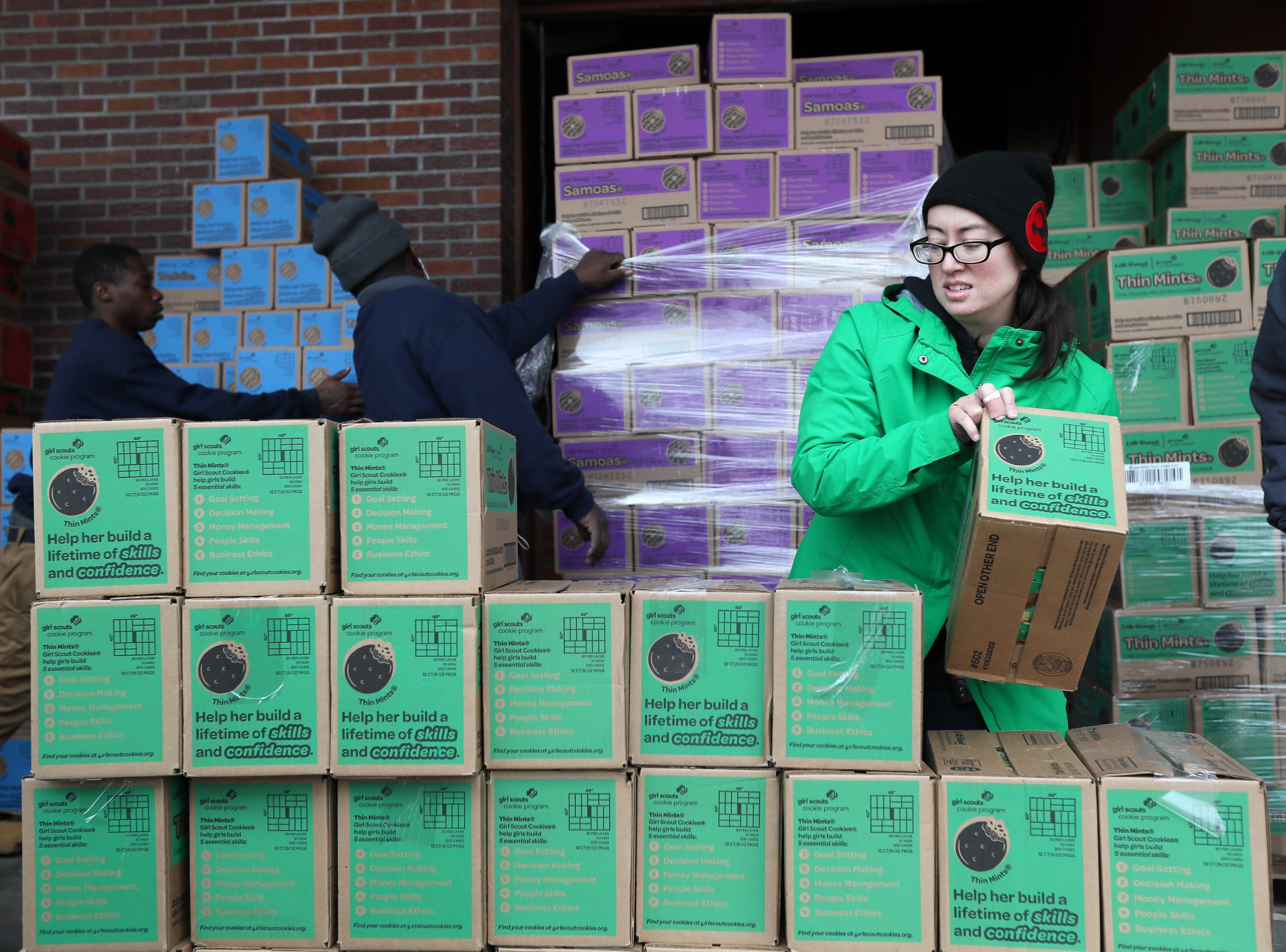 """Janet Wade of the Girl Scouts product sales team stacks boxes during the organization's """"Count N' Go"""" distribution at Armstrong Relocation where they are unloading nearly 77,000 cases of the famed cookie boxes Friday, Feb. 15, 2019."""
