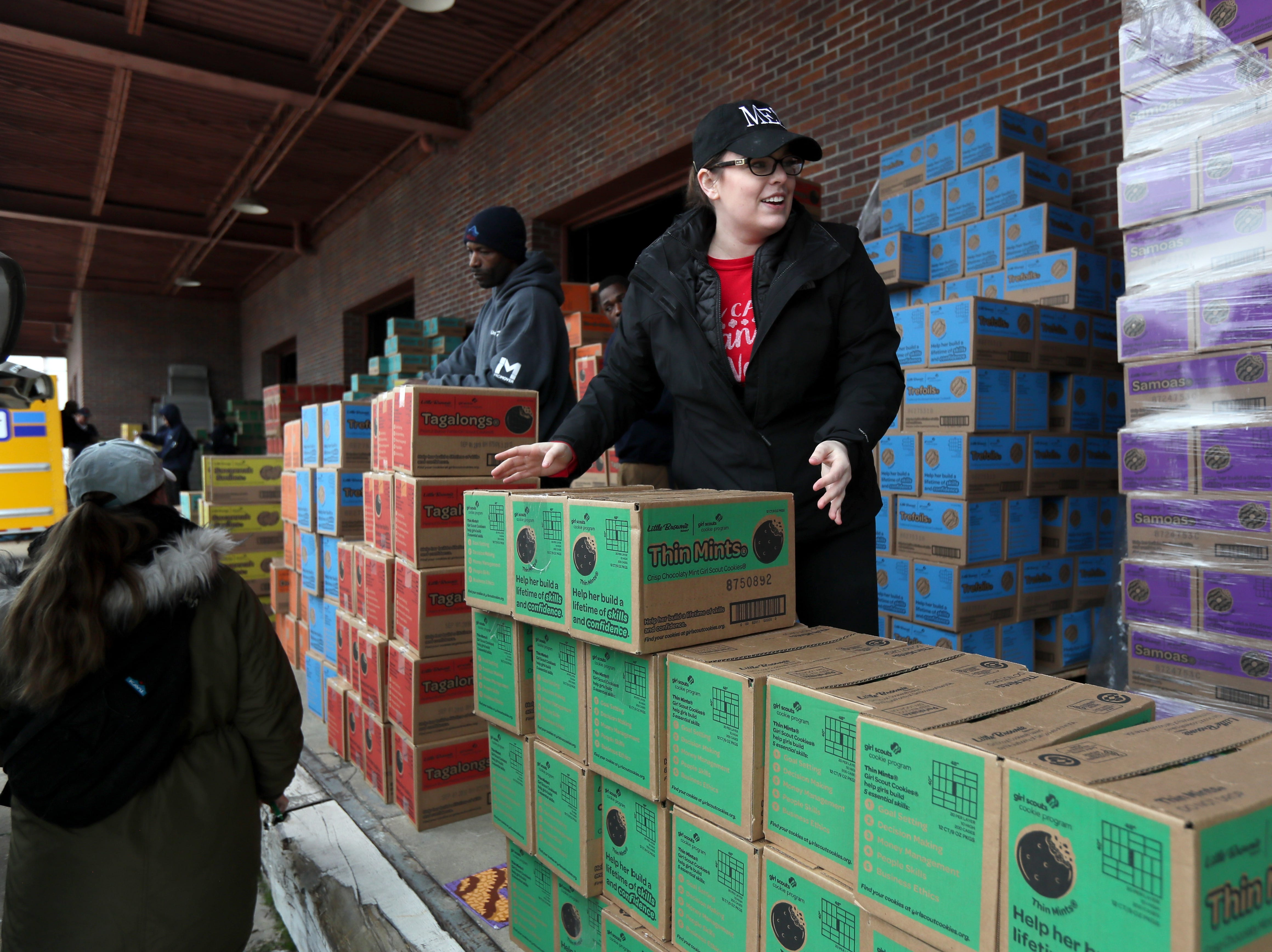 """Elizabeth Roper of the Girl Scouts events team stacks boxes during the organization's """"Count N' Go"""" distribution at Armstrong Relocation where they are unloading nearly 77,000 cases of the famed cookie boxes Friday, Feb. 15, 2019."""
