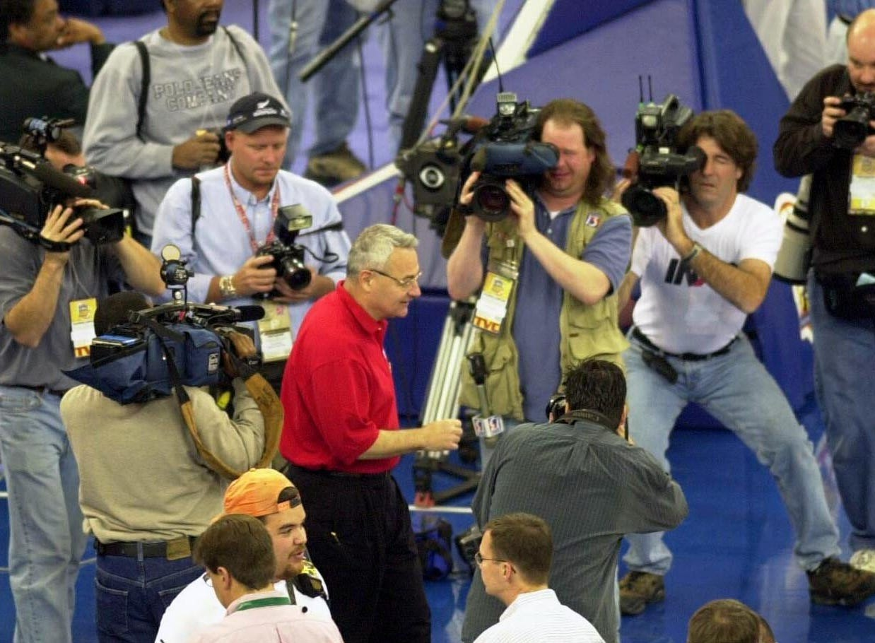 Surrounded by cameras Wisconsin Coach Dick Bennett arrives at the RCA Dome to take part on the team practice before the Final Four.