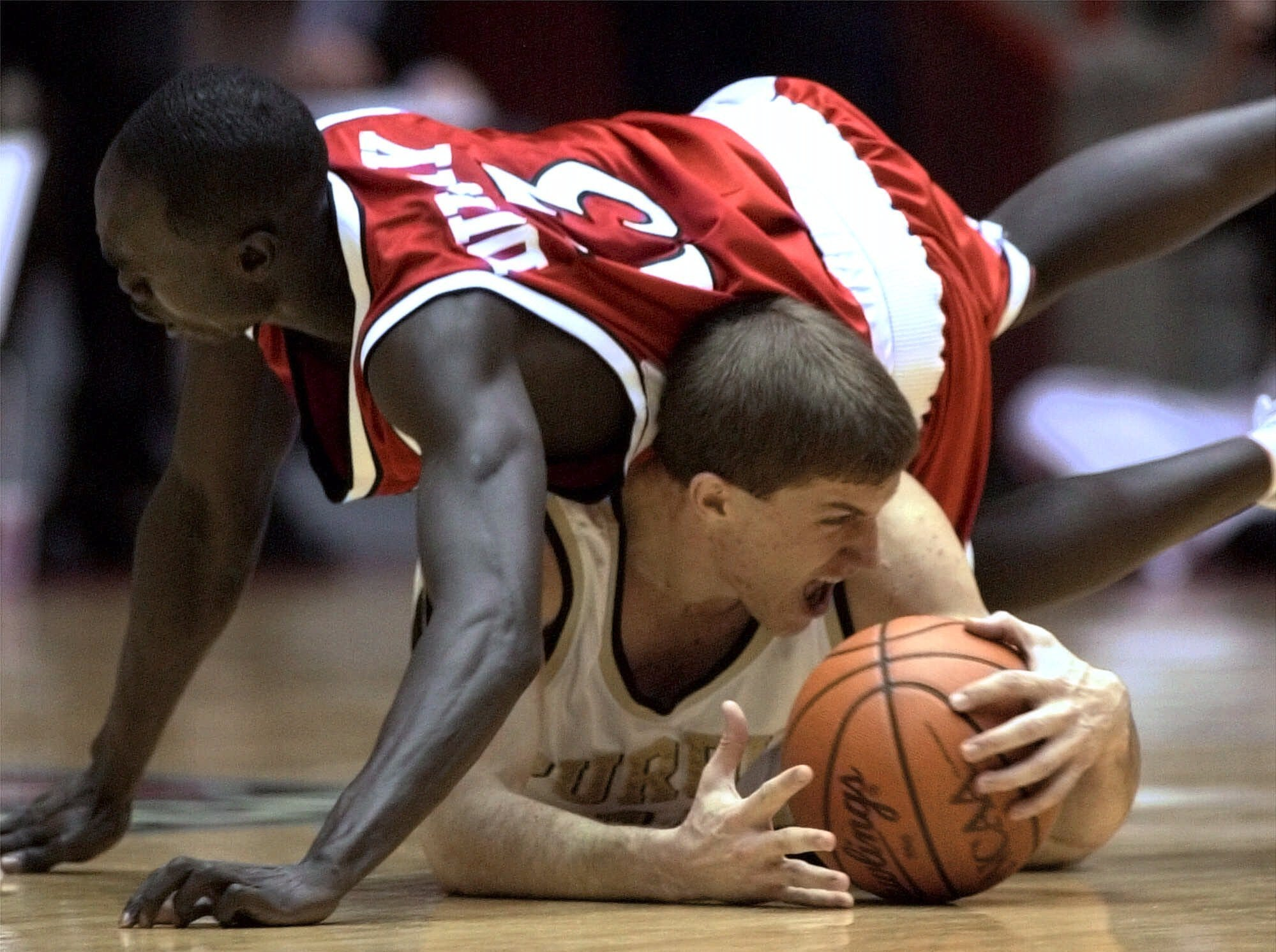 Wisconsin's Duany Duany (13) dives on Purdue's Chad Kerkhof during a scramble for a loose ball in the first half of the NCAA West Regional finals Saturday, March 25, 2000, in Albuquerque, N.M.