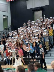 Port Washington students hold up photographs that appear as if Nicolet basketball player Jalen Johnson is in blackface.